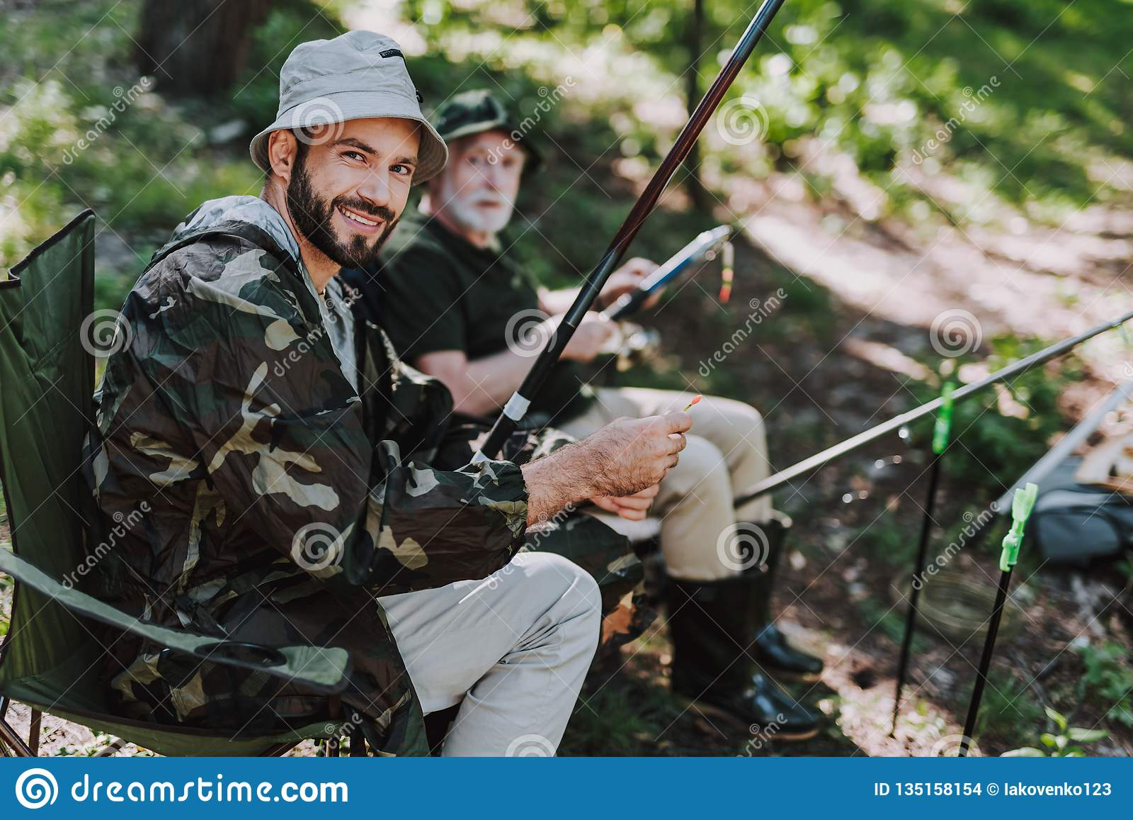 Gladlynt vuxen man som fiskar med hans pensionerade fader