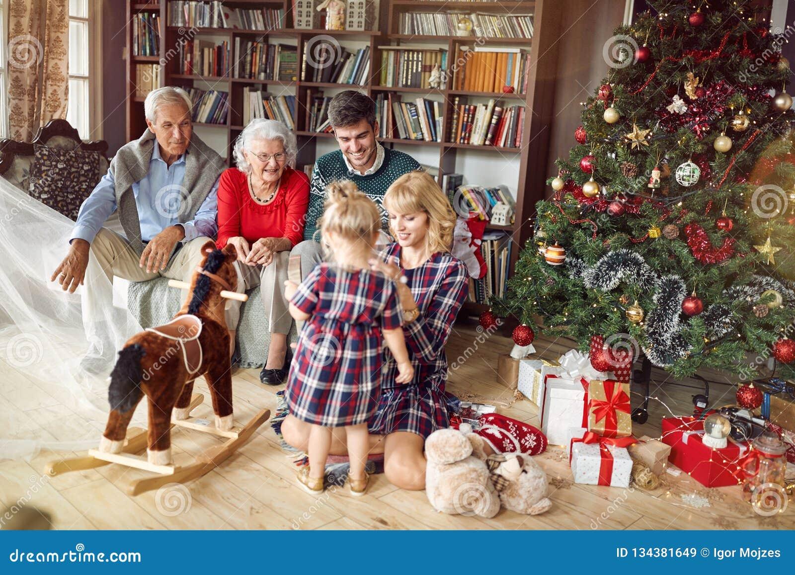 Gladlynta föräldrar med morföräldrar och lilla flickan tillsammans för jul