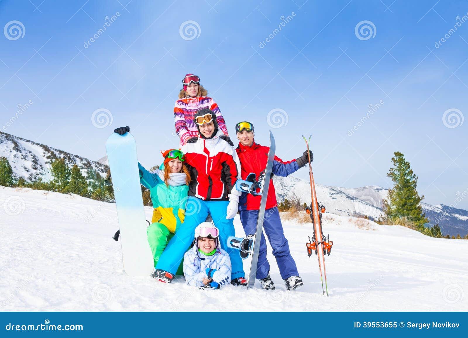 Gladlynta grabbar som står med snowboards och, skidar