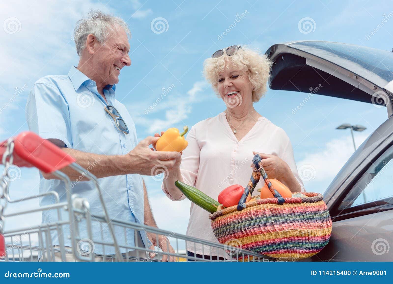 Gladlynta höga par som är lyckliga för att köpa nya grönsaker från stormarknaden