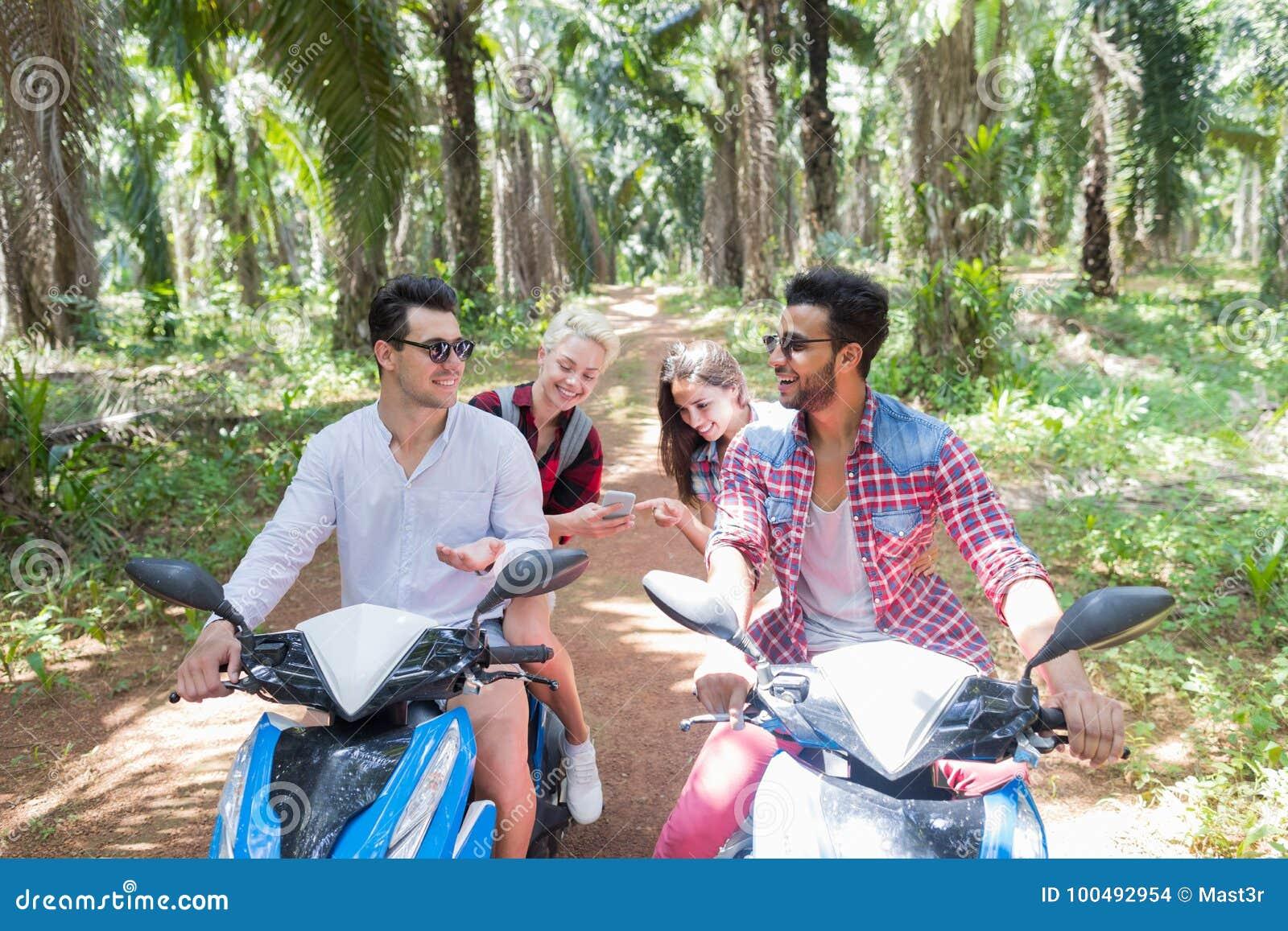 Gladlynta män som talar sammanträde på sparkcyklar, medan kvinnor som håller ögonen på foto på vänner för ungdomar för den cellSm
