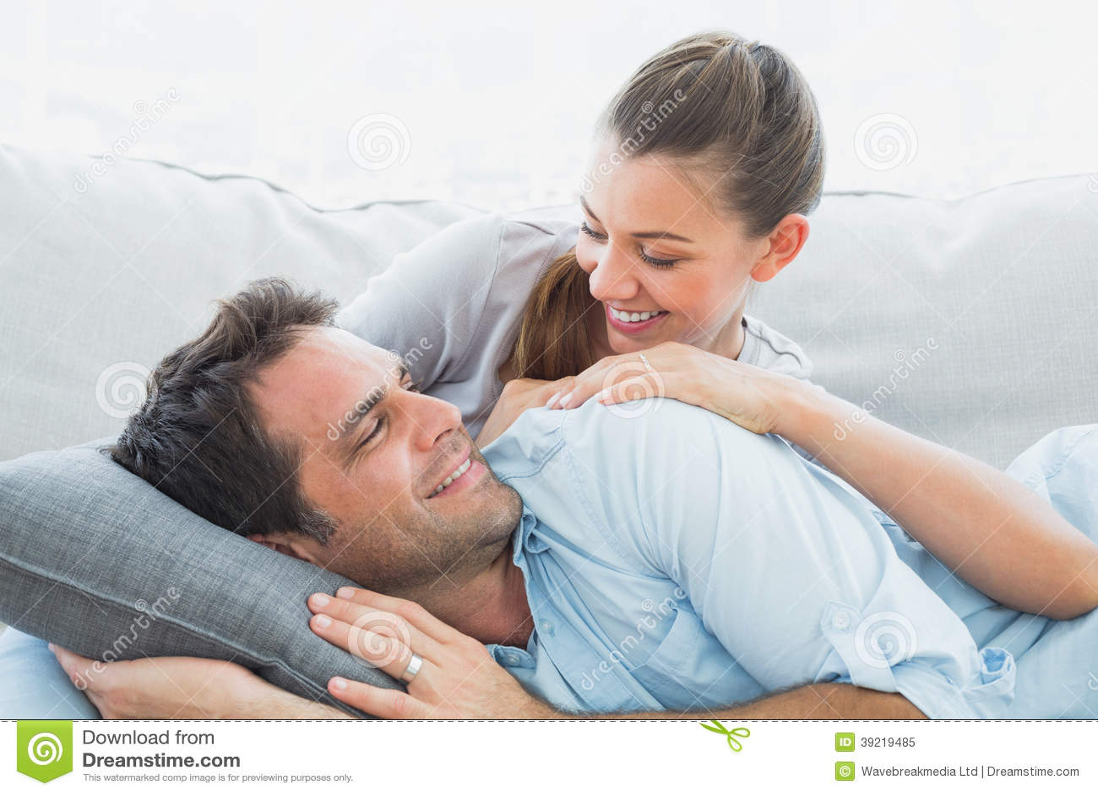 Gladlynta par som kopplar av på deras soffa som ler på de