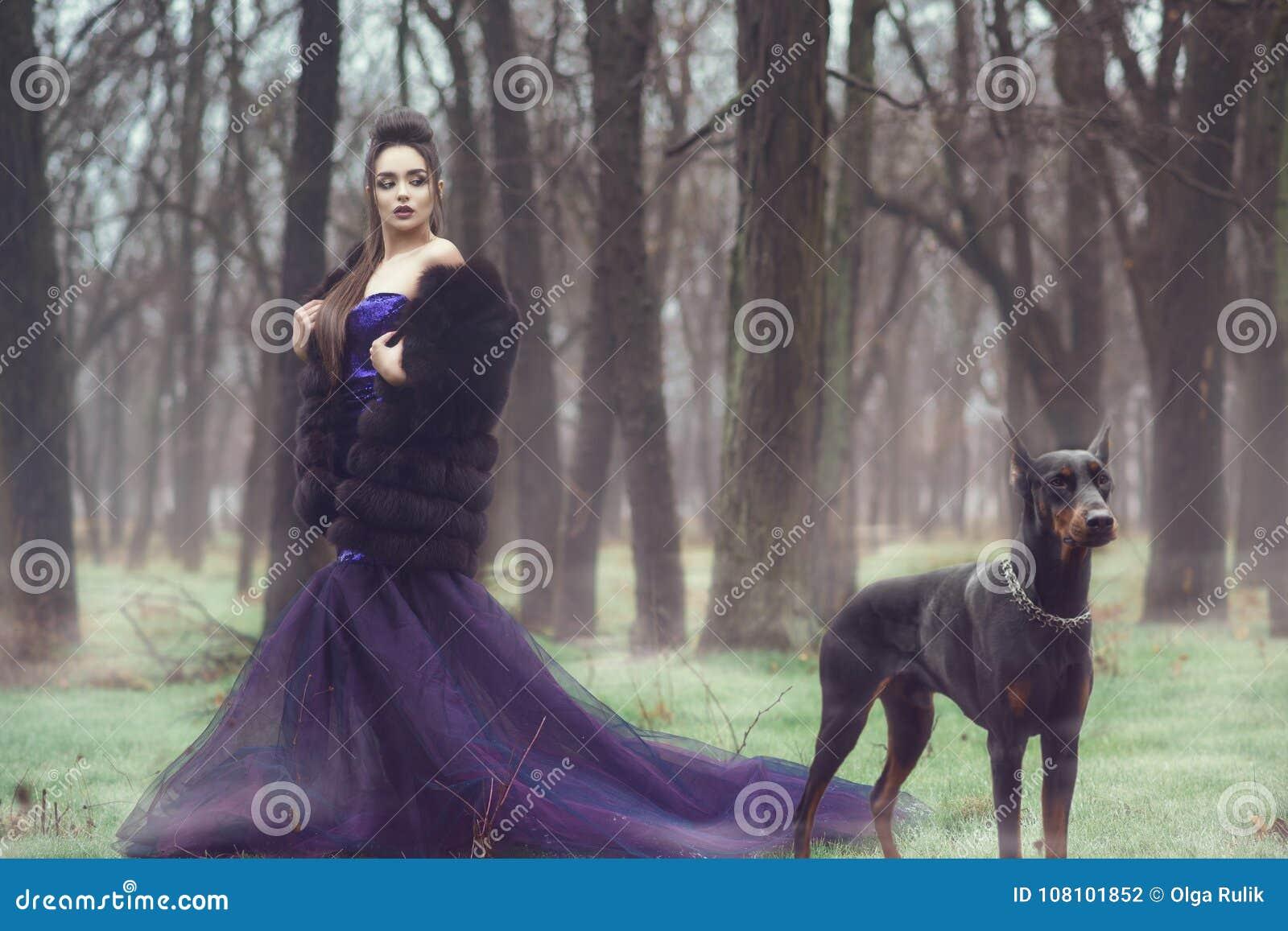 Glam dam i för aftonkappa för lyxig paljett det violetta anseendet och för pälslag i träna med hennes Dobermanpinscherhund