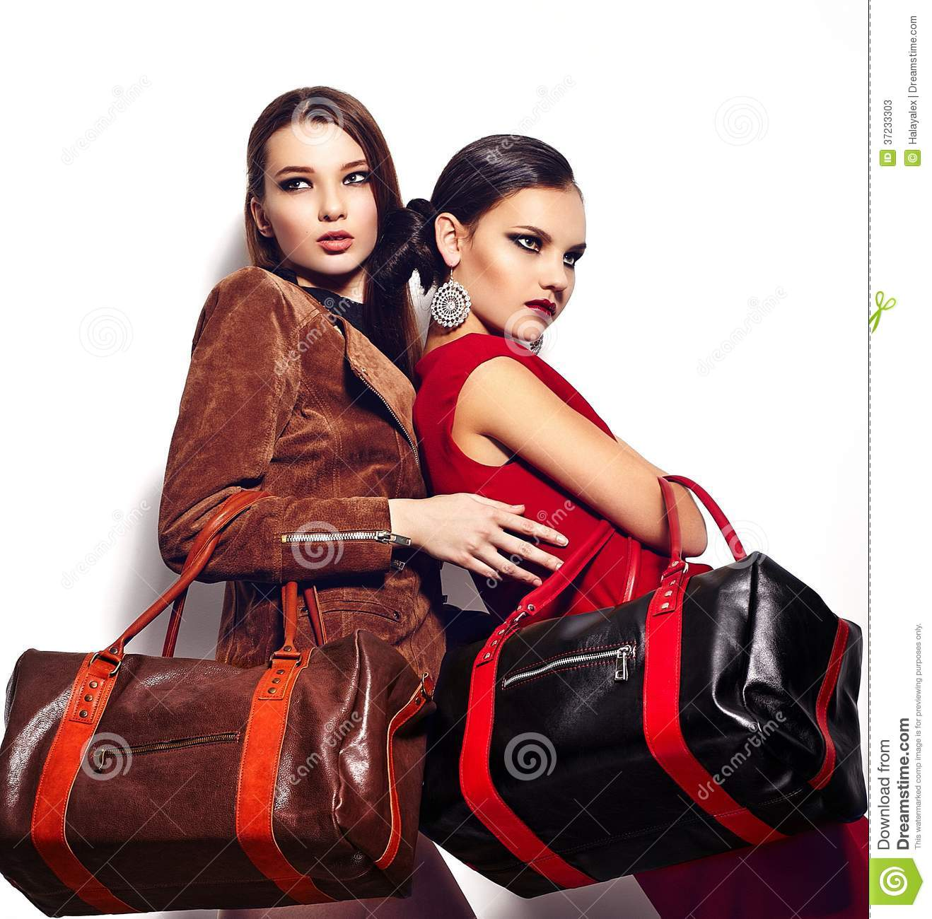 Glamor closeup portrait of two beautiful stylish brunettes Caucasian young women models with bright makeup, with red lips,