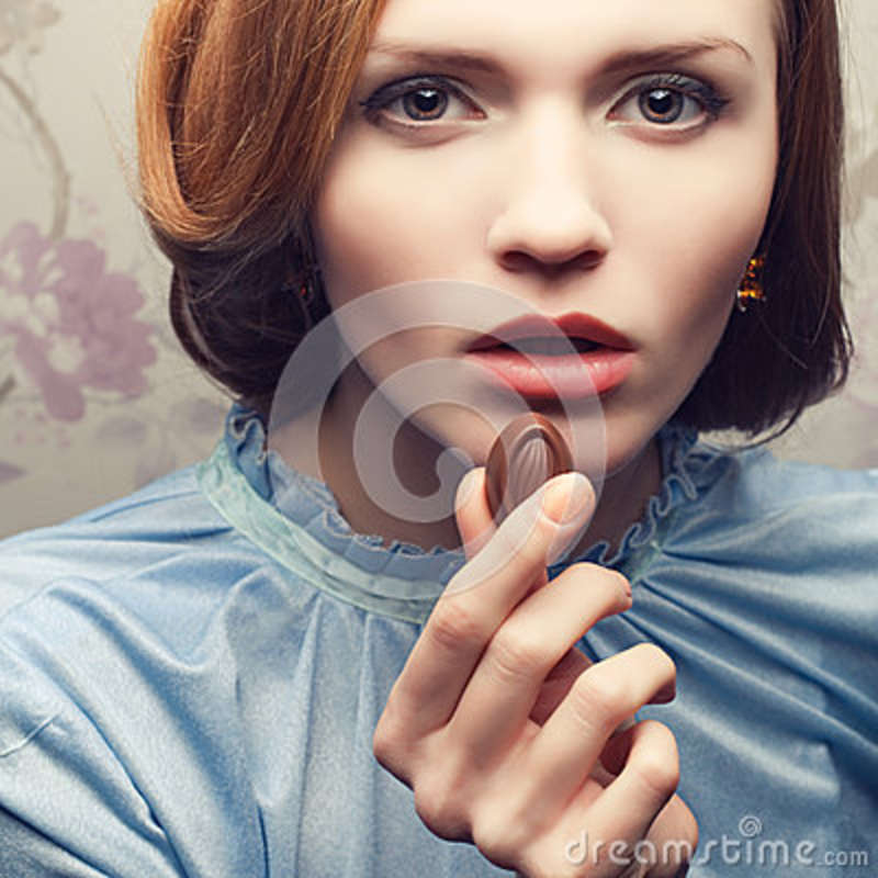 Glamorous red-haired (ginger) girl in blue dress eating candy