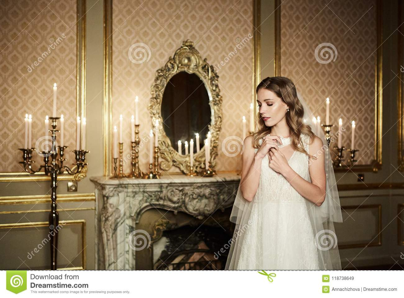Glamorous Young Bride In Wedding Dress Poses In Interior In Baroque