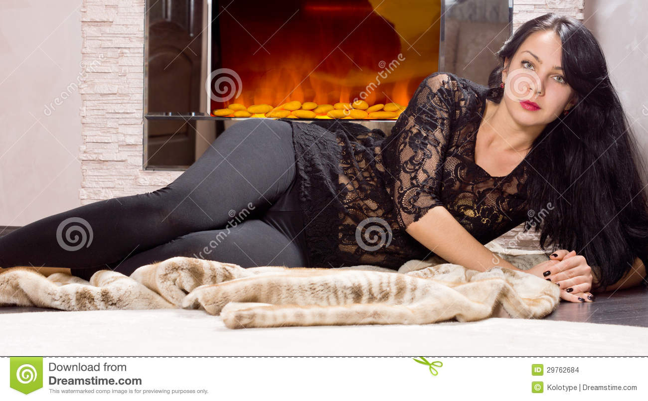 Glamorous Woman Lying In Front Of A Fire Stock Images