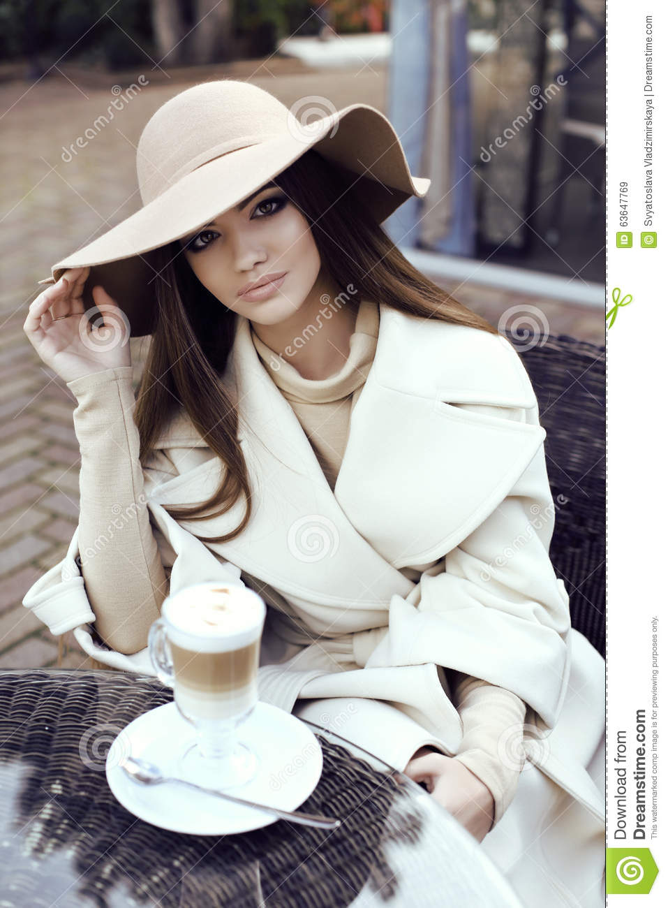 Glamour girl with dark straight hair wears luxurious beige coat with elegant hat,