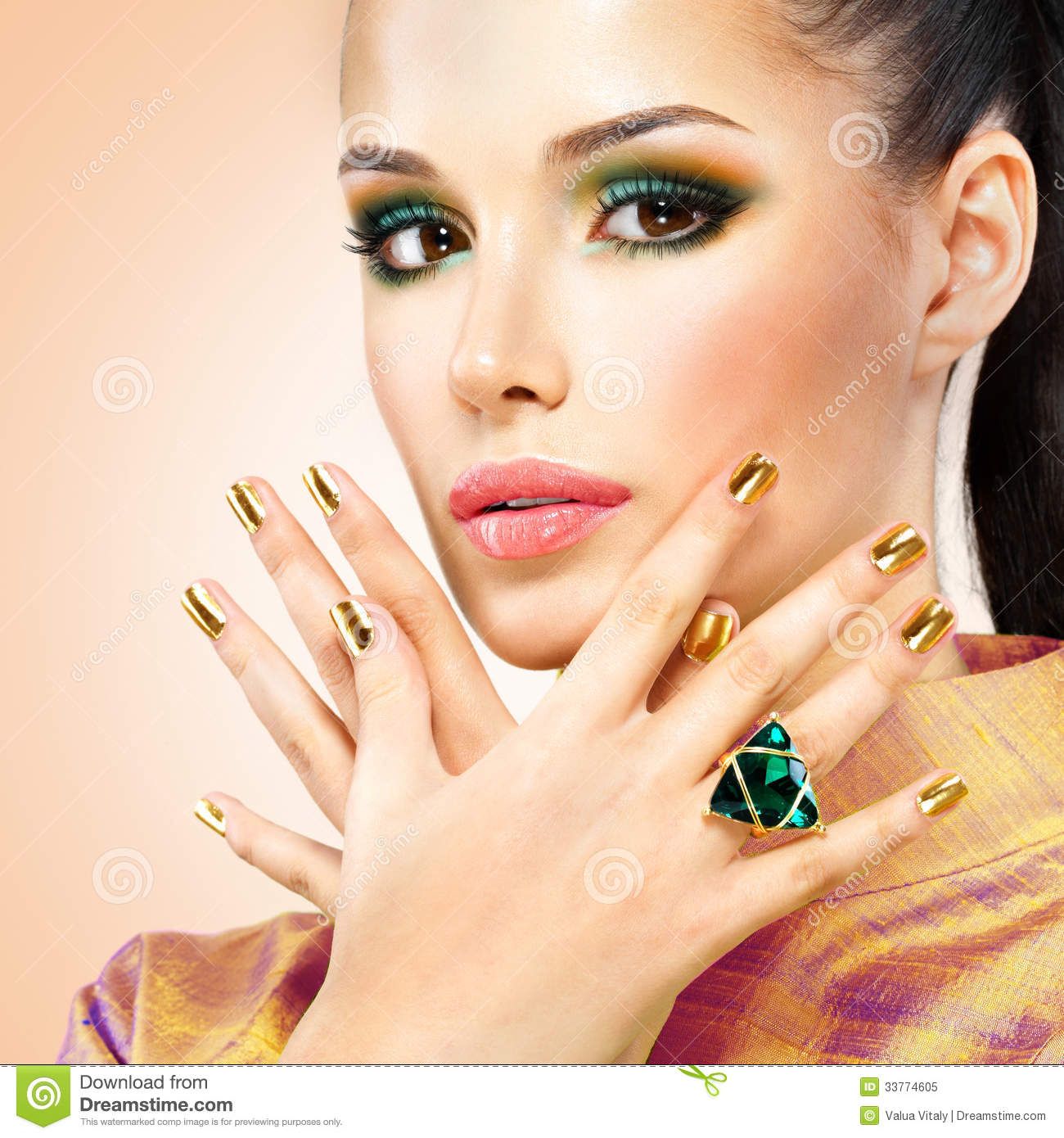 glamour woman with beautiful golden nails and emerald ring royalty