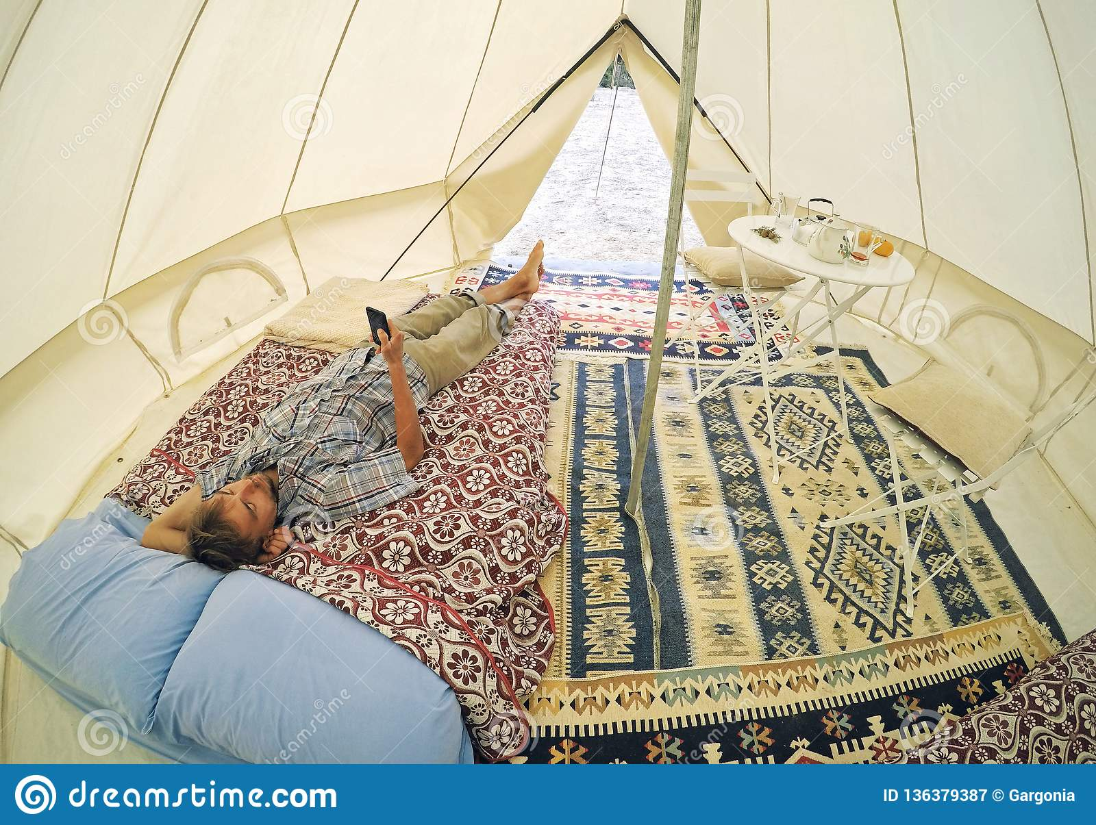 Glamping outdoor accomodation. Tourist men with smartphone lying on bed inside camping tent with cozy interior