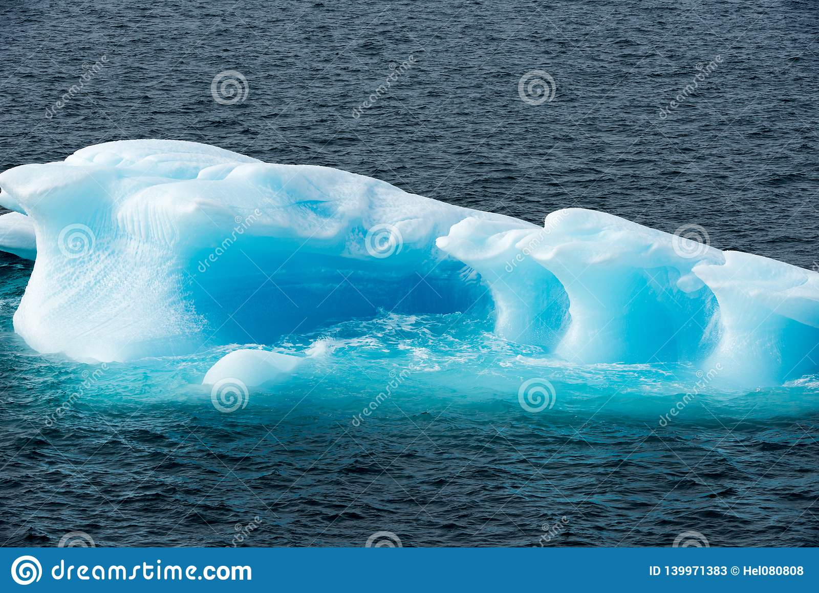 Glanzende turkooise Ijsberg die door turkoois glanzend water, Groenland wordt omringd