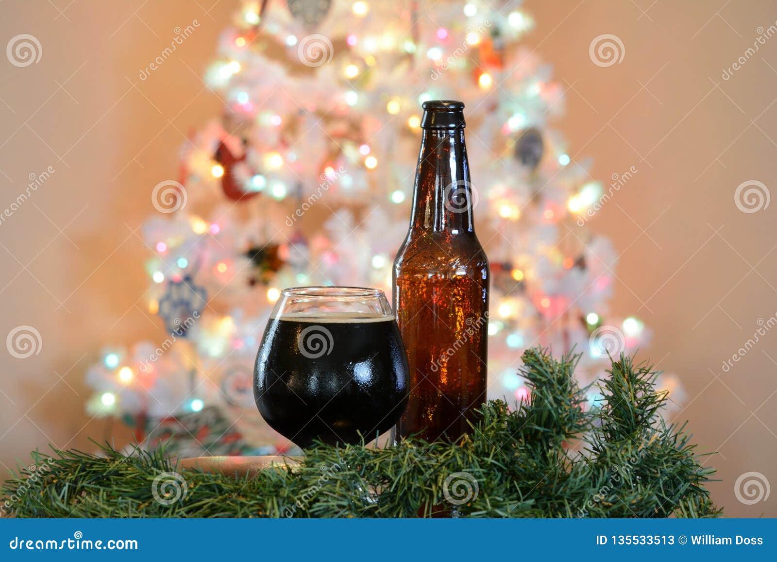 Glas Bier aufgeworfen vor Baum der weißen Weihnacht mit farbigen Lichtern