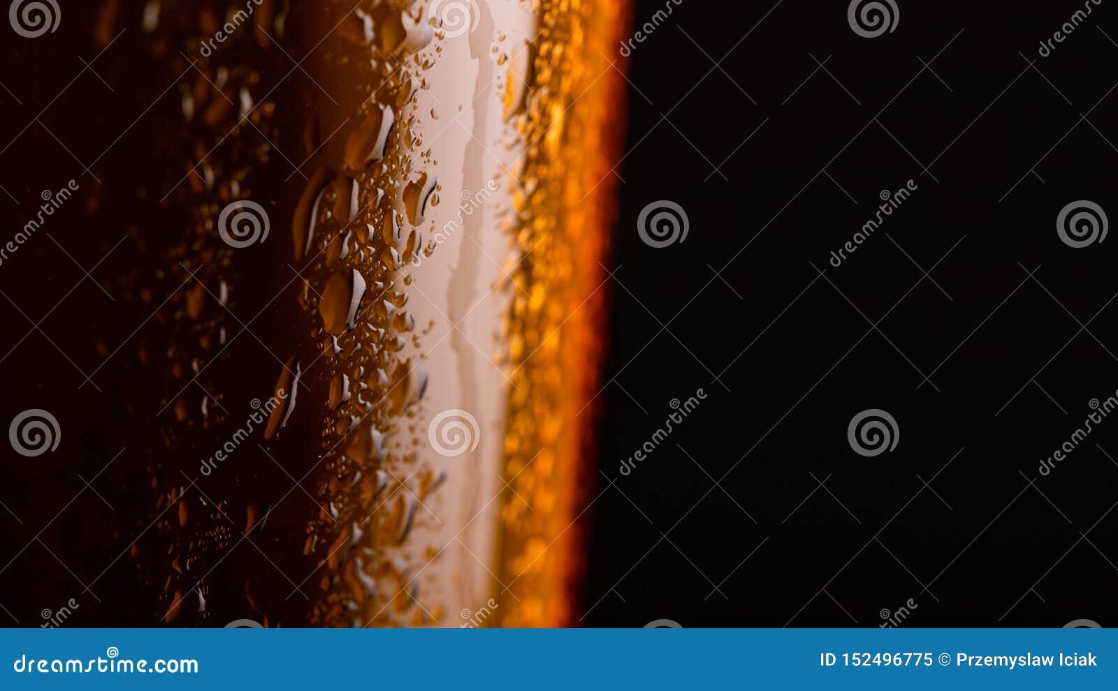 Glas bier met schuim op zwarte close-up als achtergrond