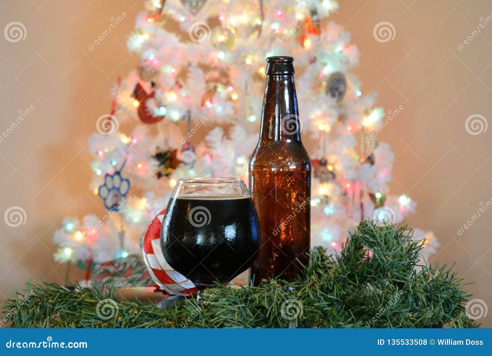 Glas bier voor witte Kerstboom met gekleurde lichten wordt gesteld dat