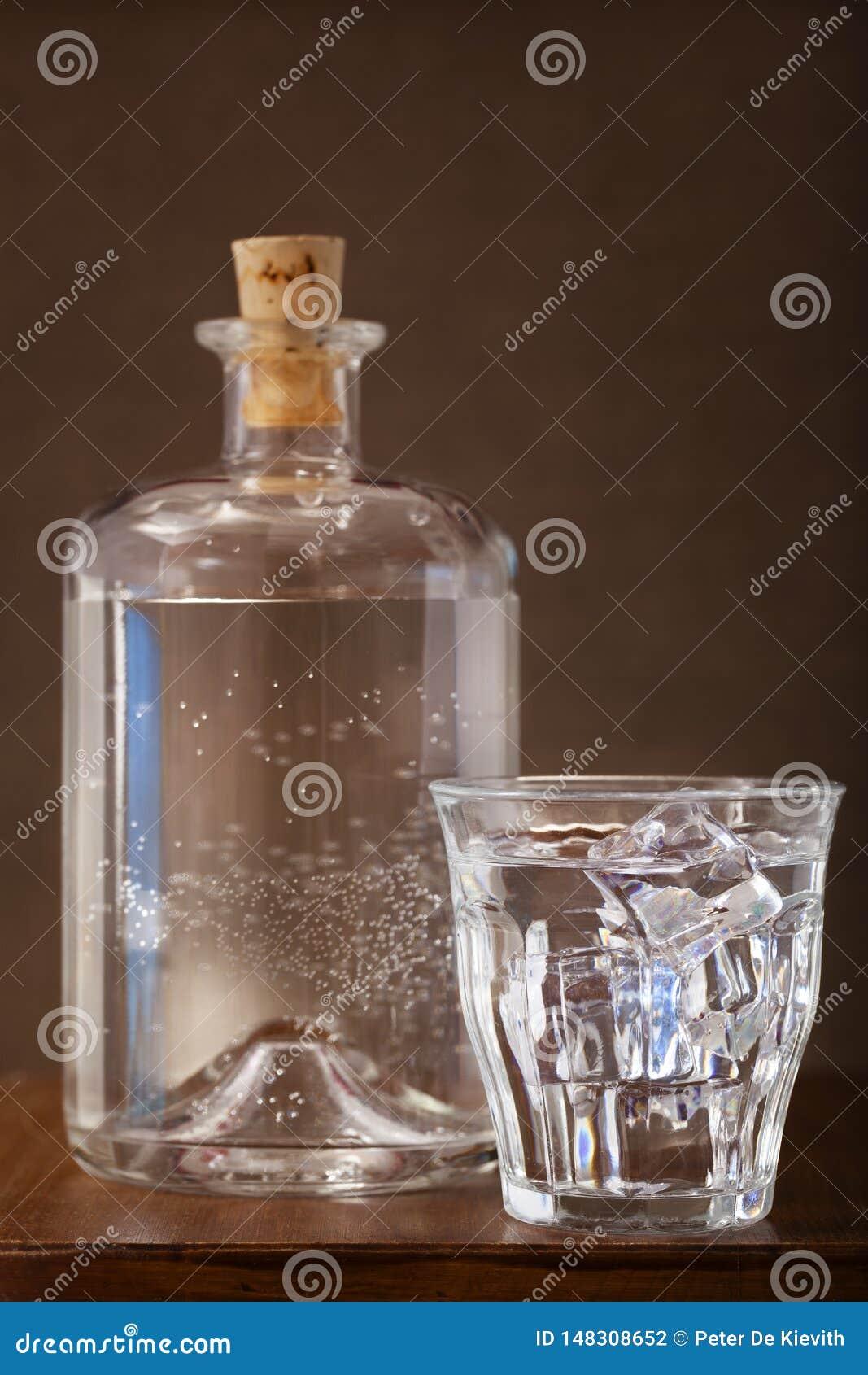 Glas des eiskalten Wassers und der Flasche