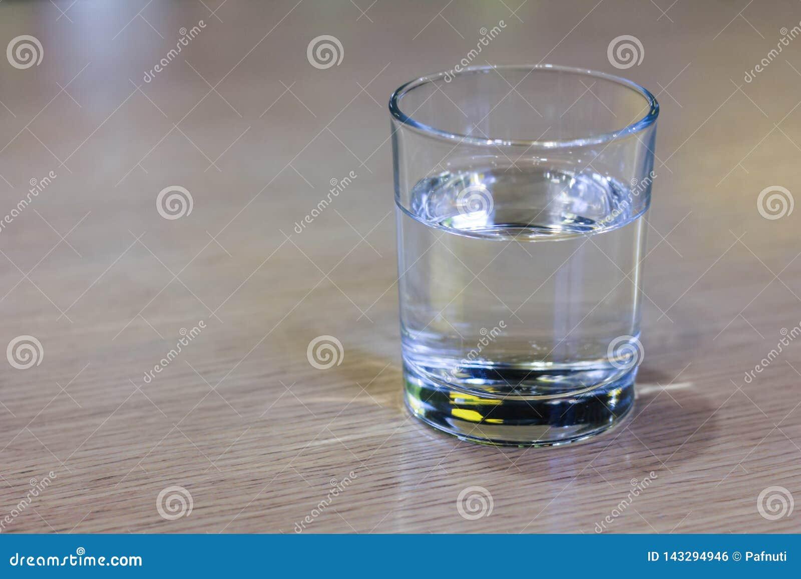 Glas duidelijk water op houten lijst