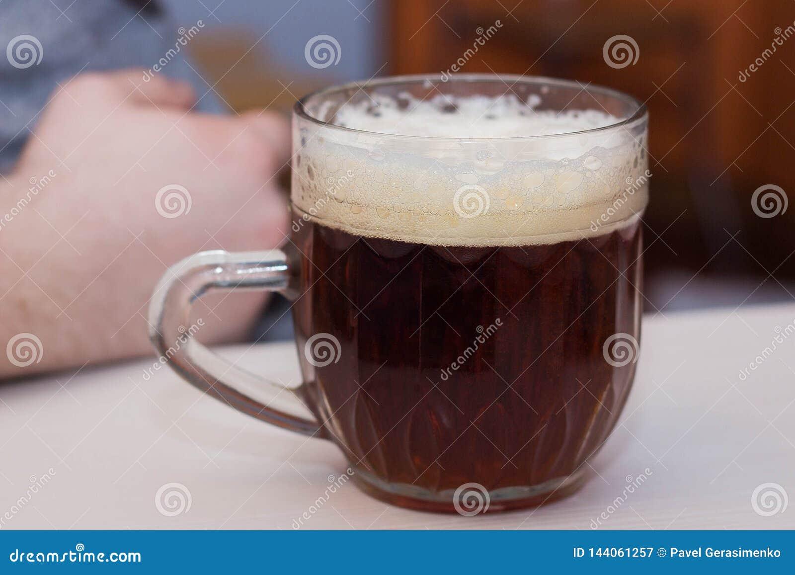 Glas dunkles Bier, gesalzene Erdnüsse