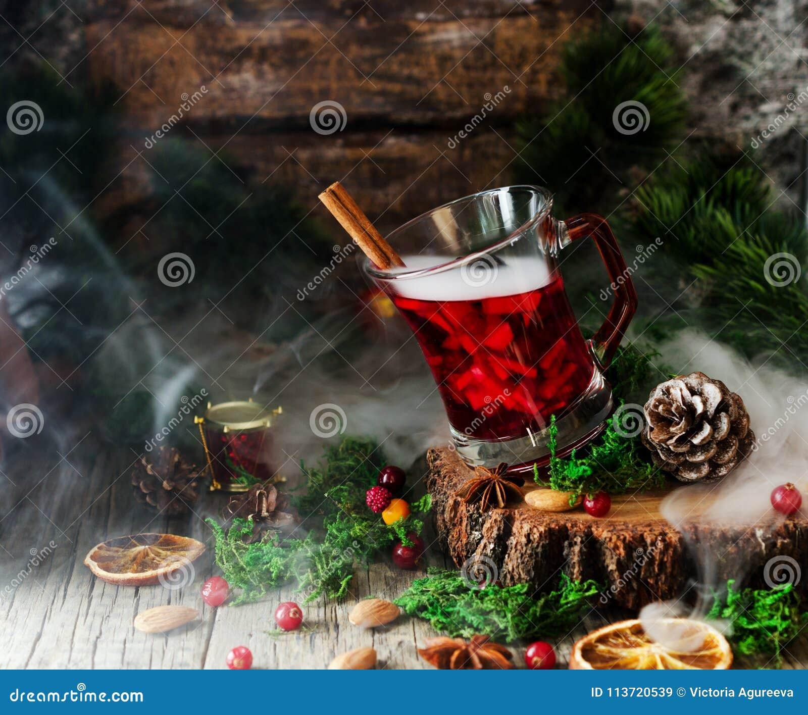 Glas heißer Glühwein für das neue Jahr mit Bestandteilen für das Kochen, die Nüsse und die Weihnachtsdekorationen