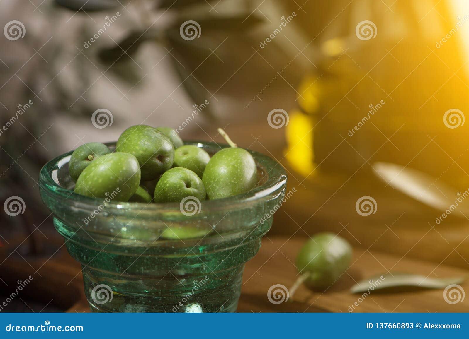 Glas kopp av oliv med extra jungfrulig olivolja i glasflaska på lantlig bakgrund close upp