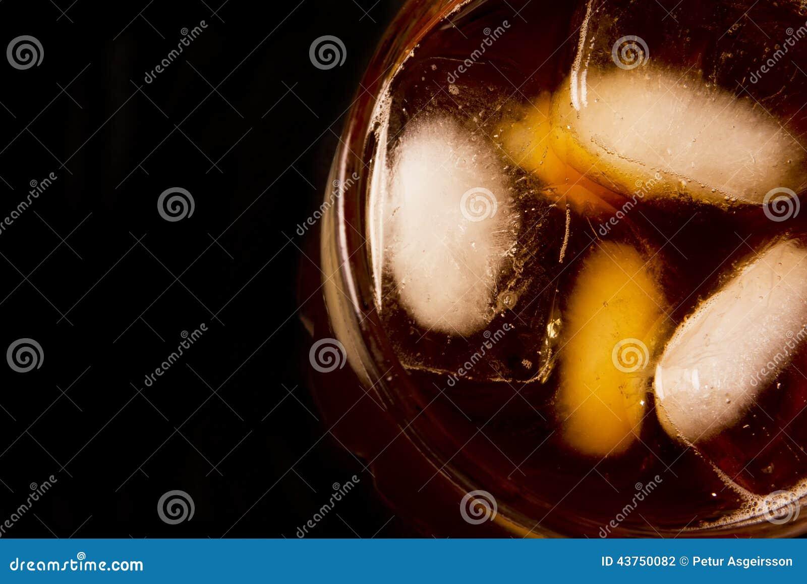 Glas met donker vloeibaar hoogtepunt met ijsblokjes