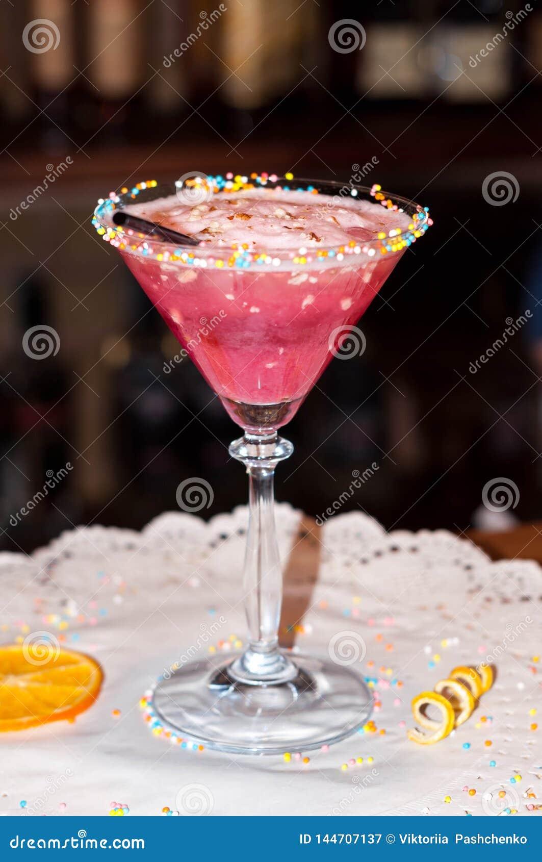 Glas met rode alcoholdrank en stro op Witboekservet met droge oranje plak