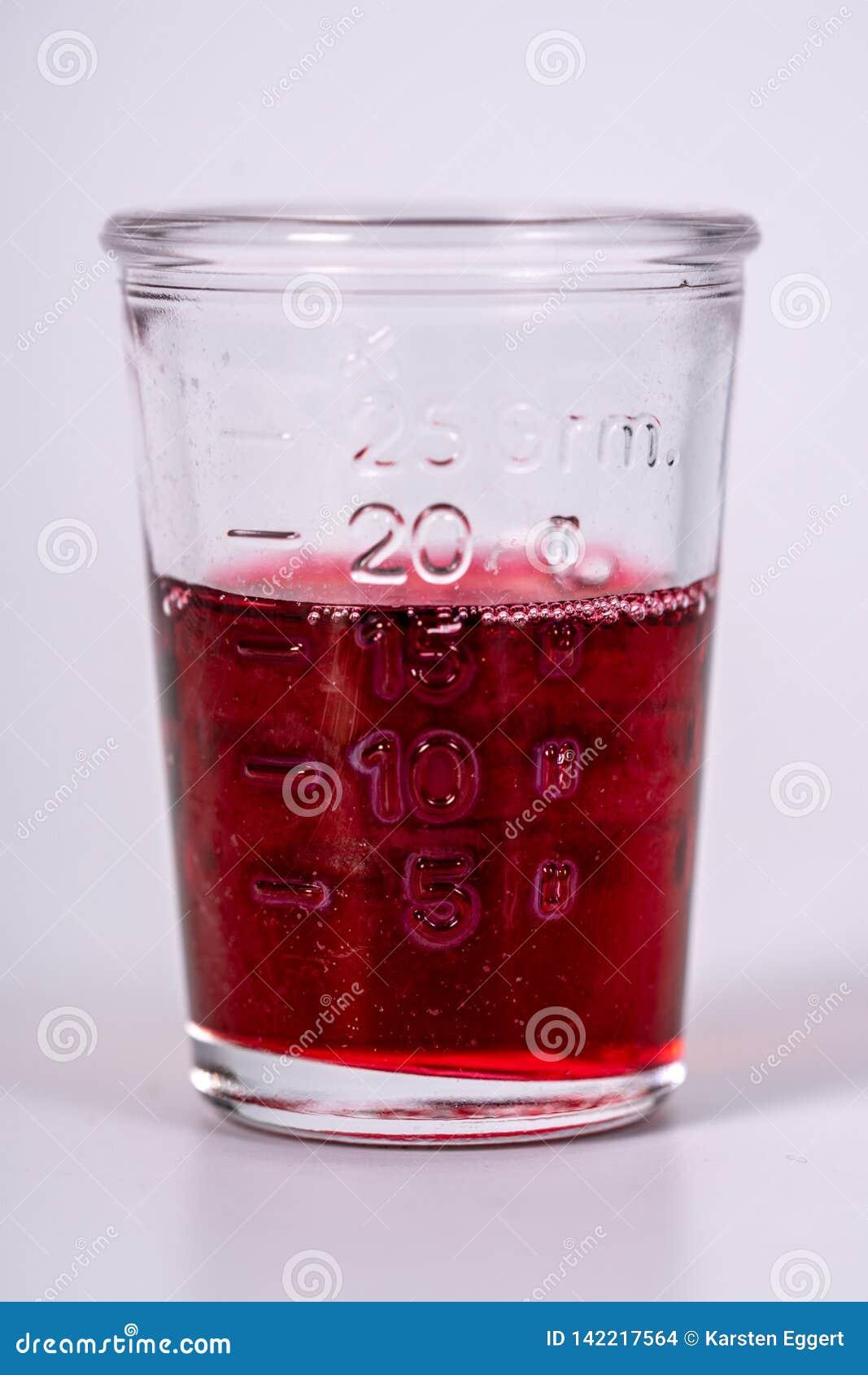 Glas met rode geneeskunde wordt gevuld die