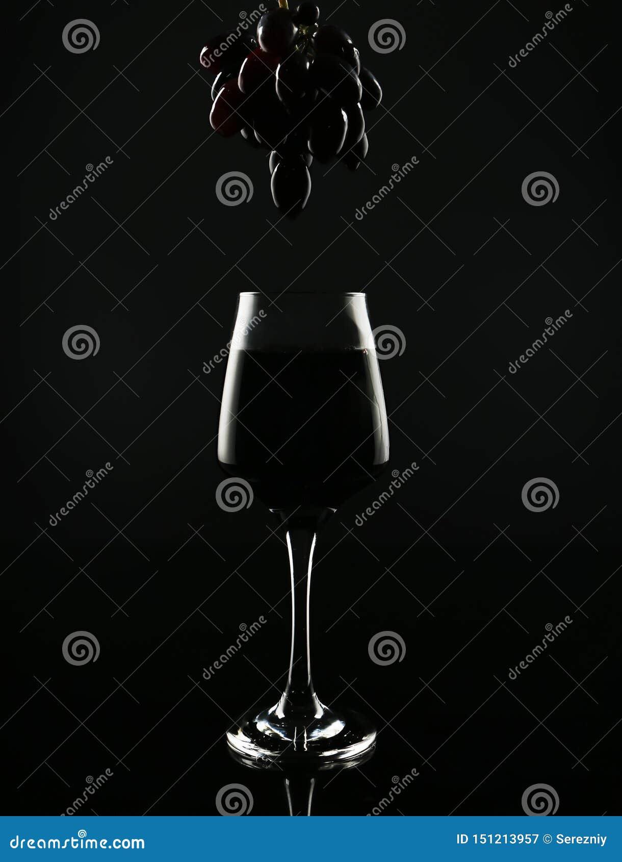 Glas met rode wijn en smakelijke verse druiven op zwarte achtergrond