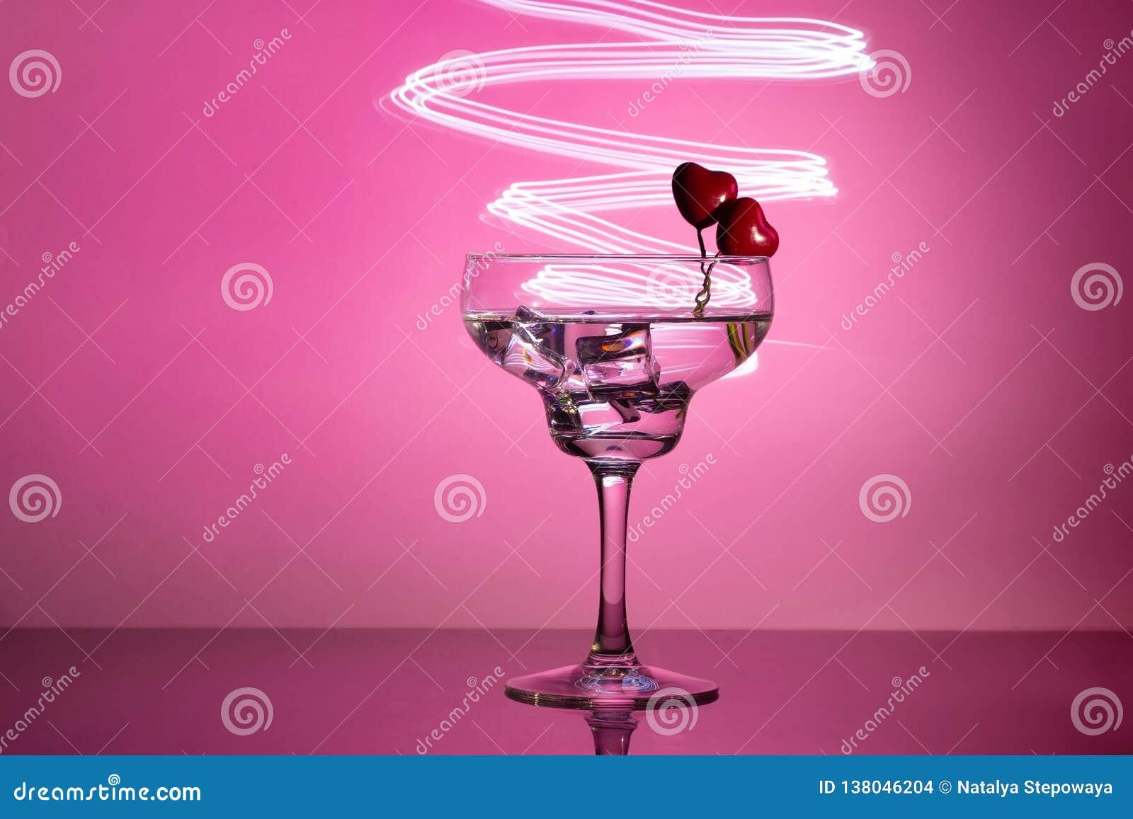 Glas mit einem Cocktail und zwei Herzen Valentinstag und Hochzeitskonzept