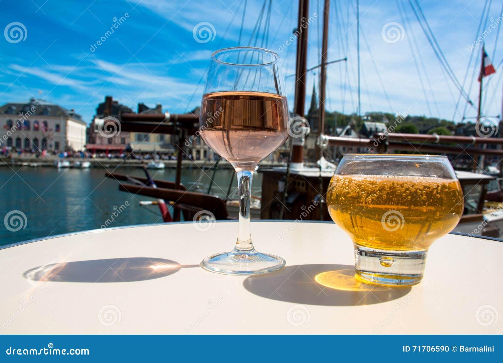 Glas mit geschmackvollem Apfelwein und rosafarbener Rebe im alten französischen fisherm