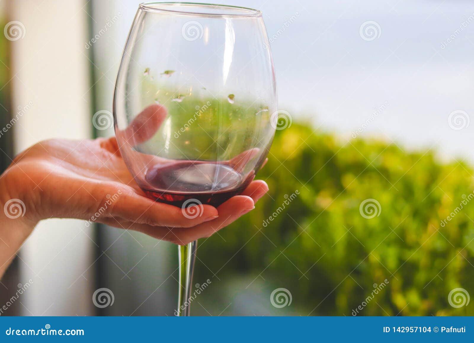 Glas rode wijn in de hand bij het proeven