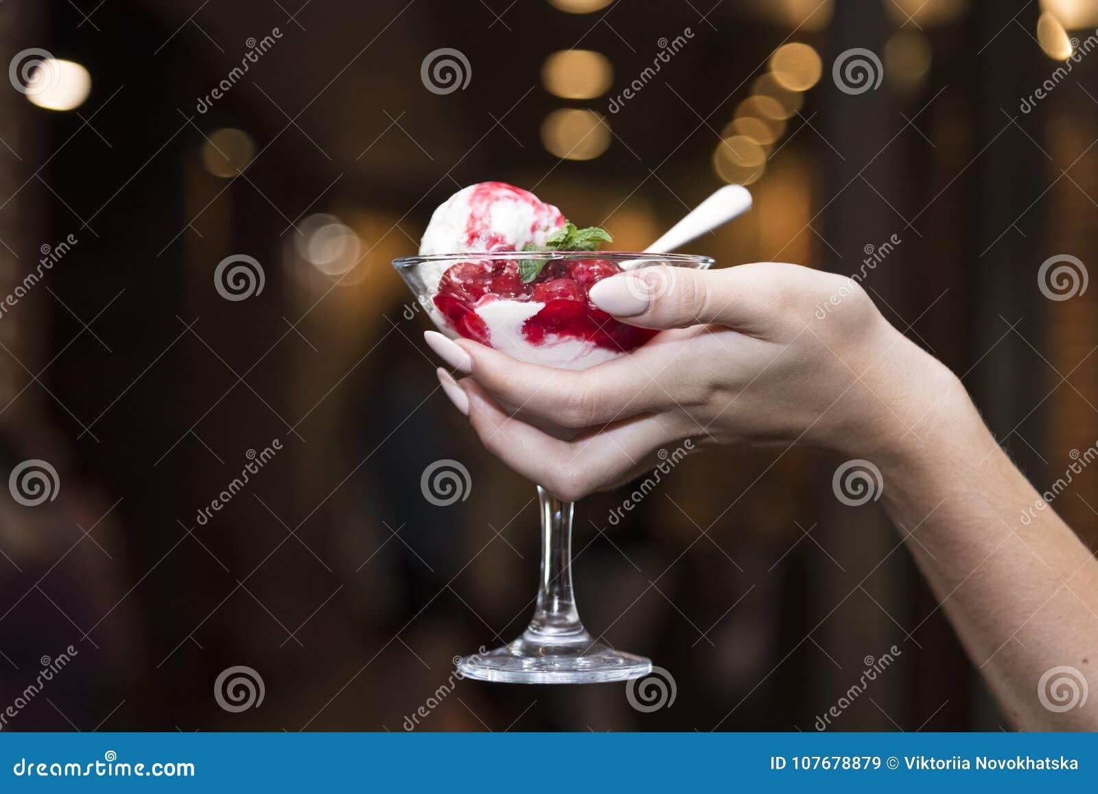 Glas roomijs met fruit in de handen van een gir