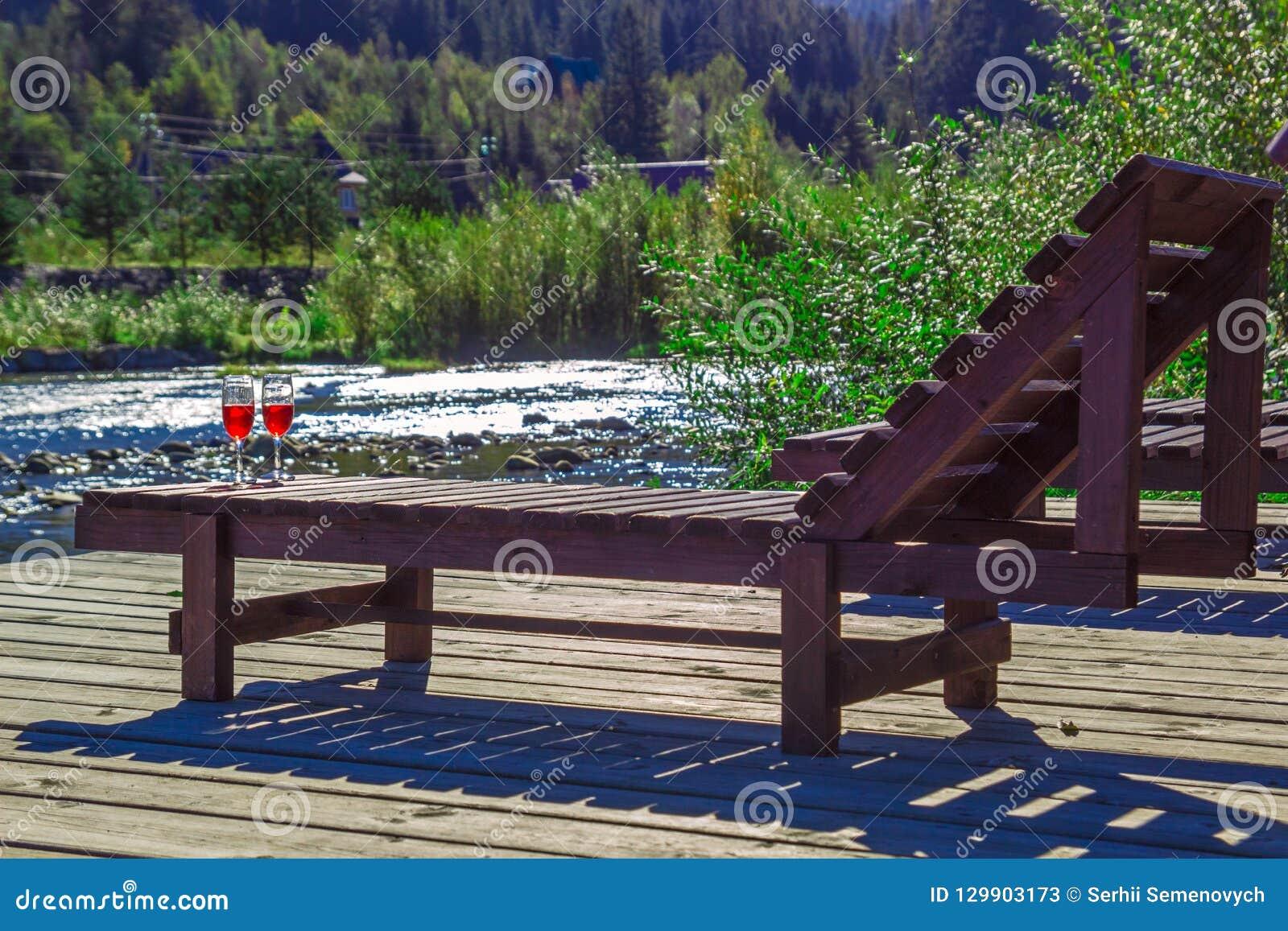 Glas Rotwein auf dem Hintergrund von einem Gebirgsfluss Hölzerner Wagenaufenthaltsraum, Berge, Luxusfeiertag