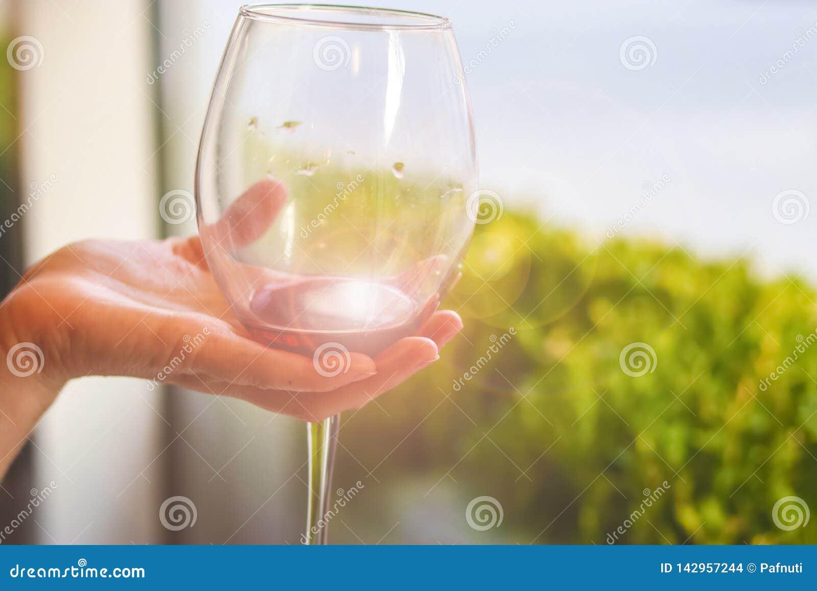 Glas Rotwein in der Hand am Probieren