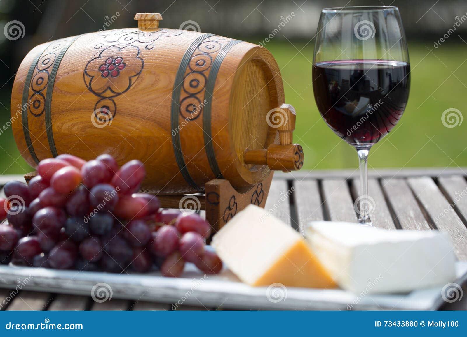 Glas Rotwein mit Trauben auf Holztisch