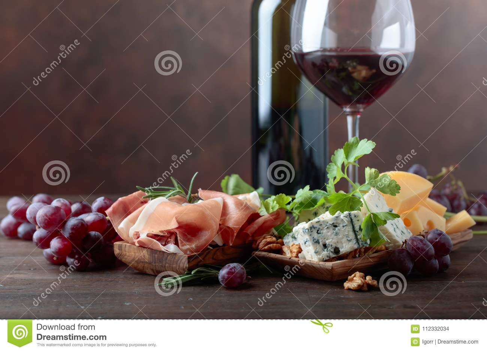 Glas Rotwein mit verschiedenen Käsen, Früchten und Prosciutto