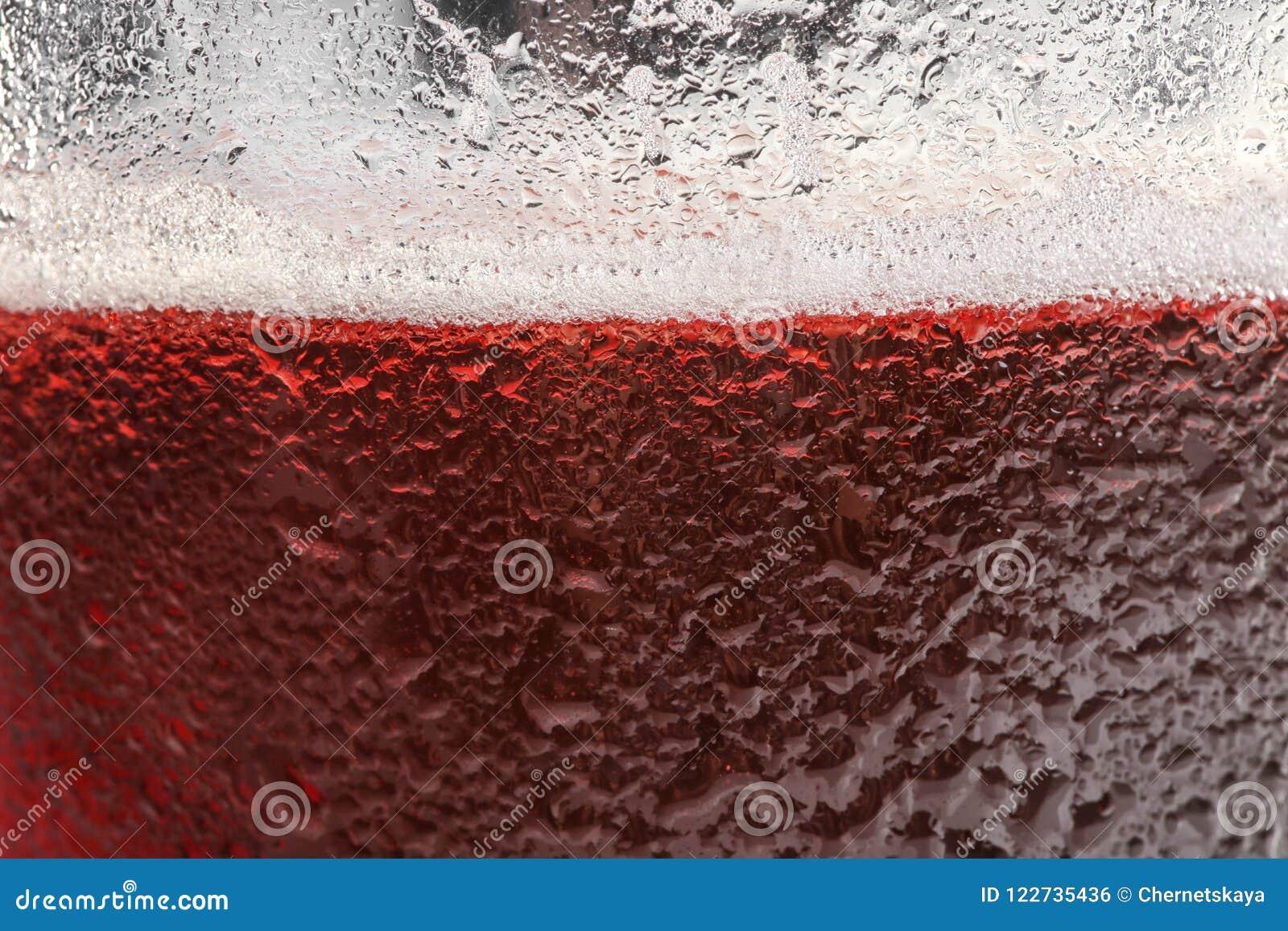 Glas smakelijk rood bier met schuimclose-up