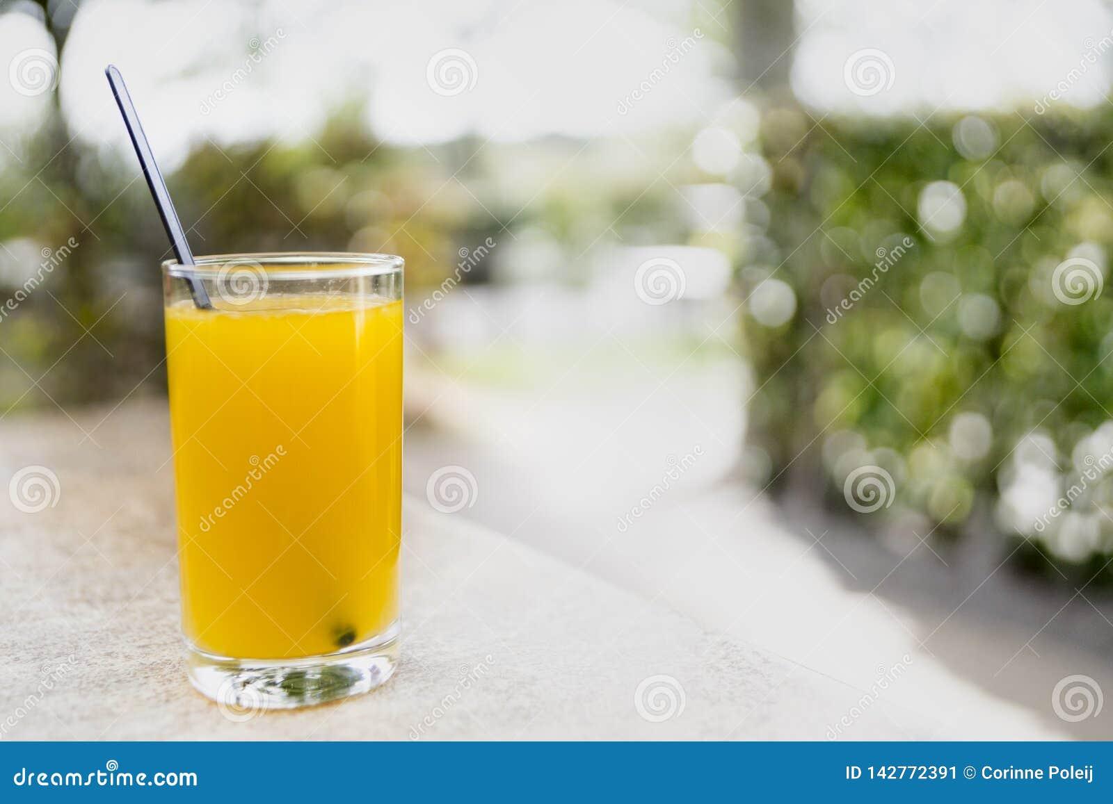 Glas vers jus d orange met zwarte lepel op lijst