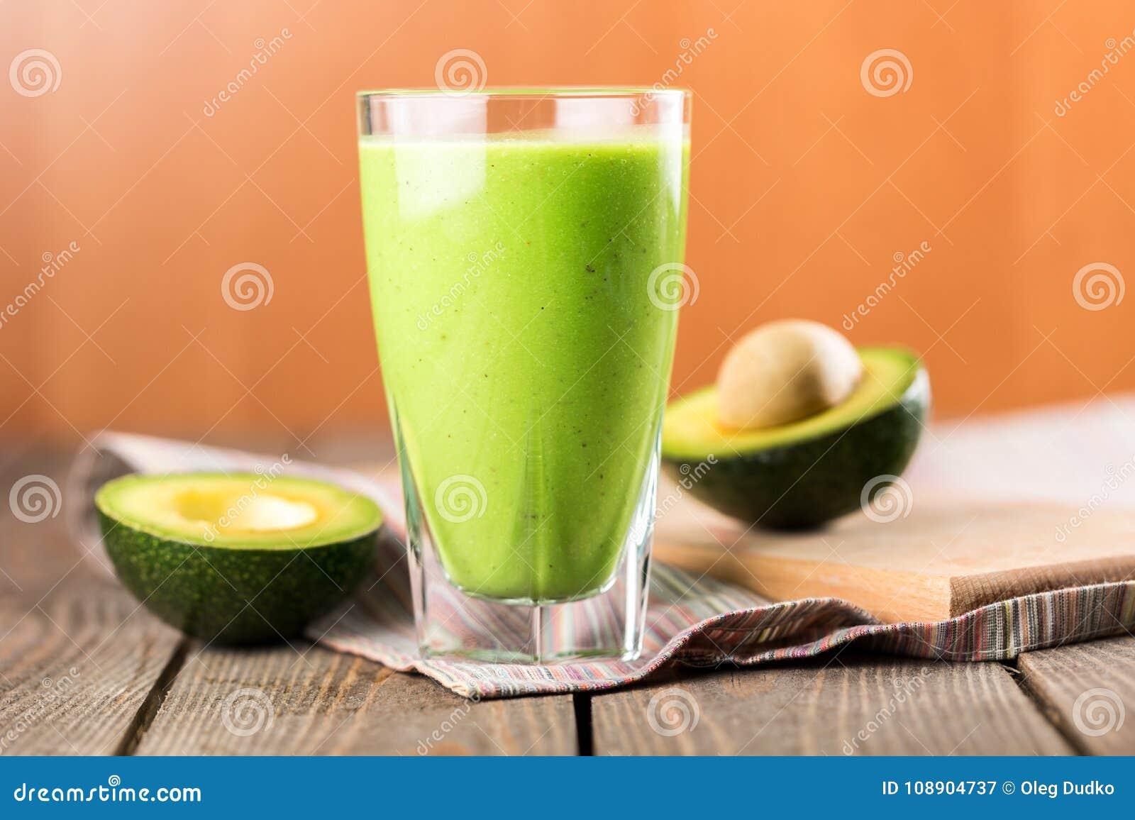 Glas verse sap en avocadohelften op houten