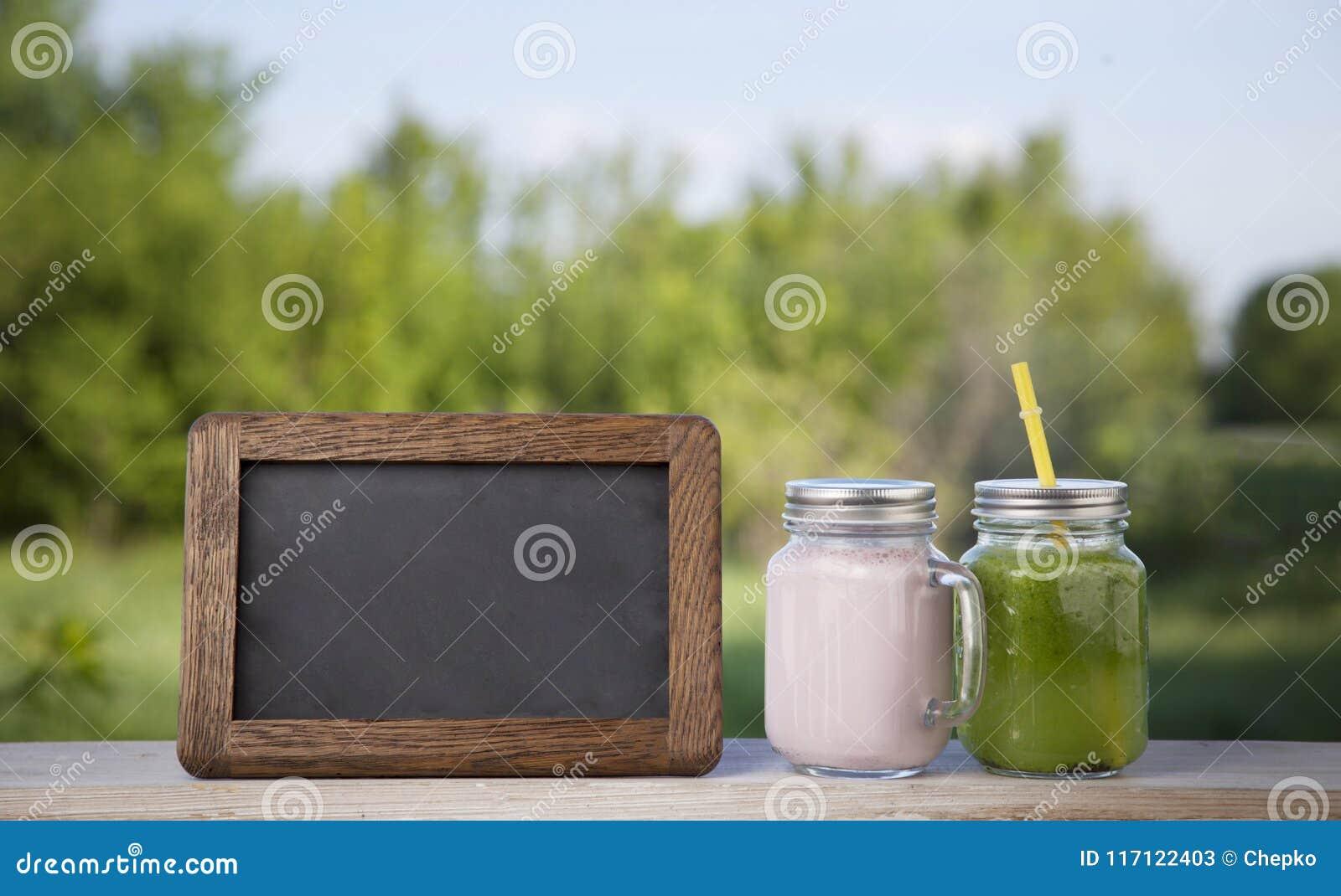 Glas von detoxsmoothie und tafel auf holztisch im ga stockbild