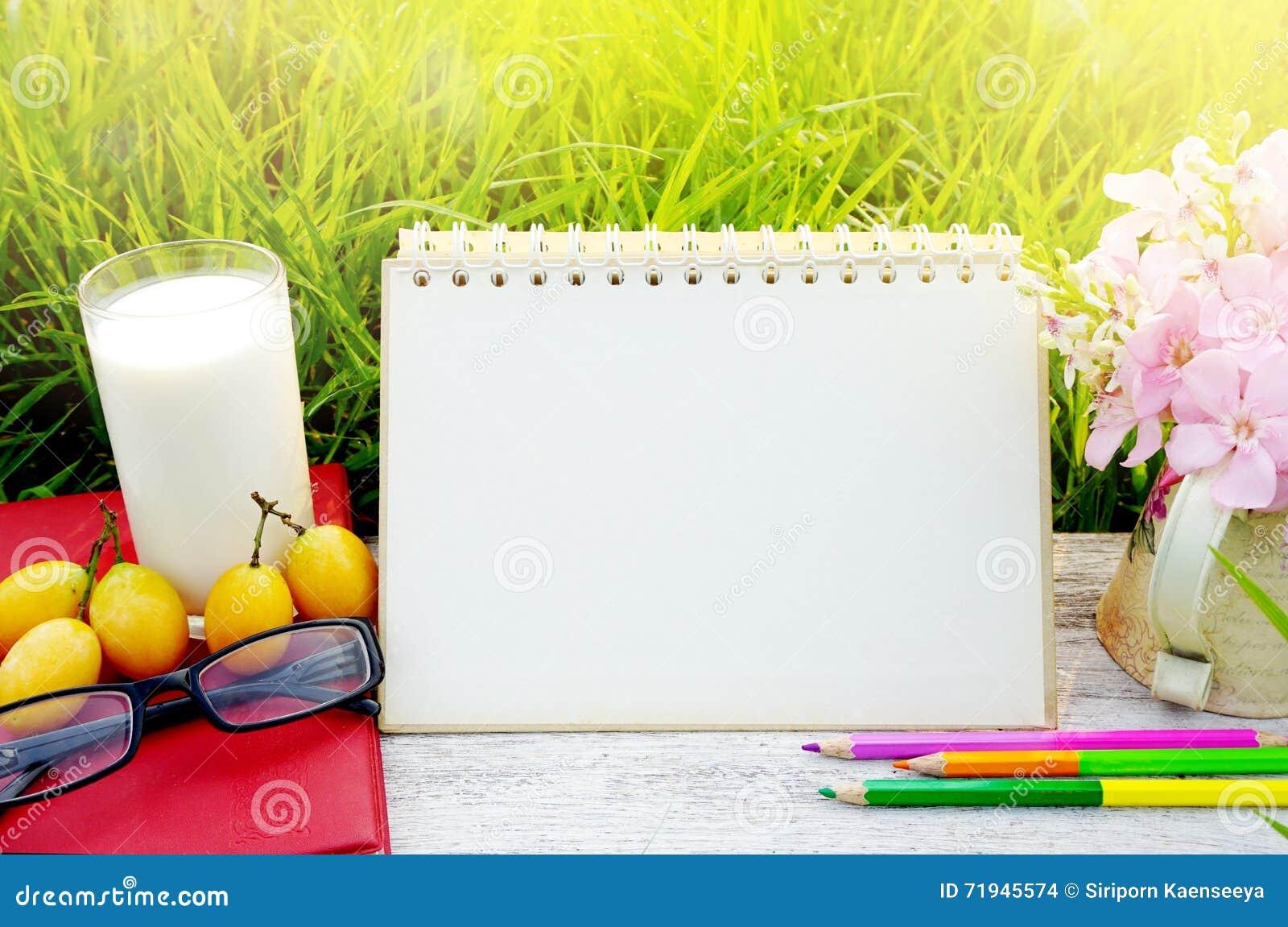 Glas von Milch, von Leerseitenkalender, von gelber Frucht, von Sonnenbrille, von Bleistiften und von rosa Blume auf weißer hölzer