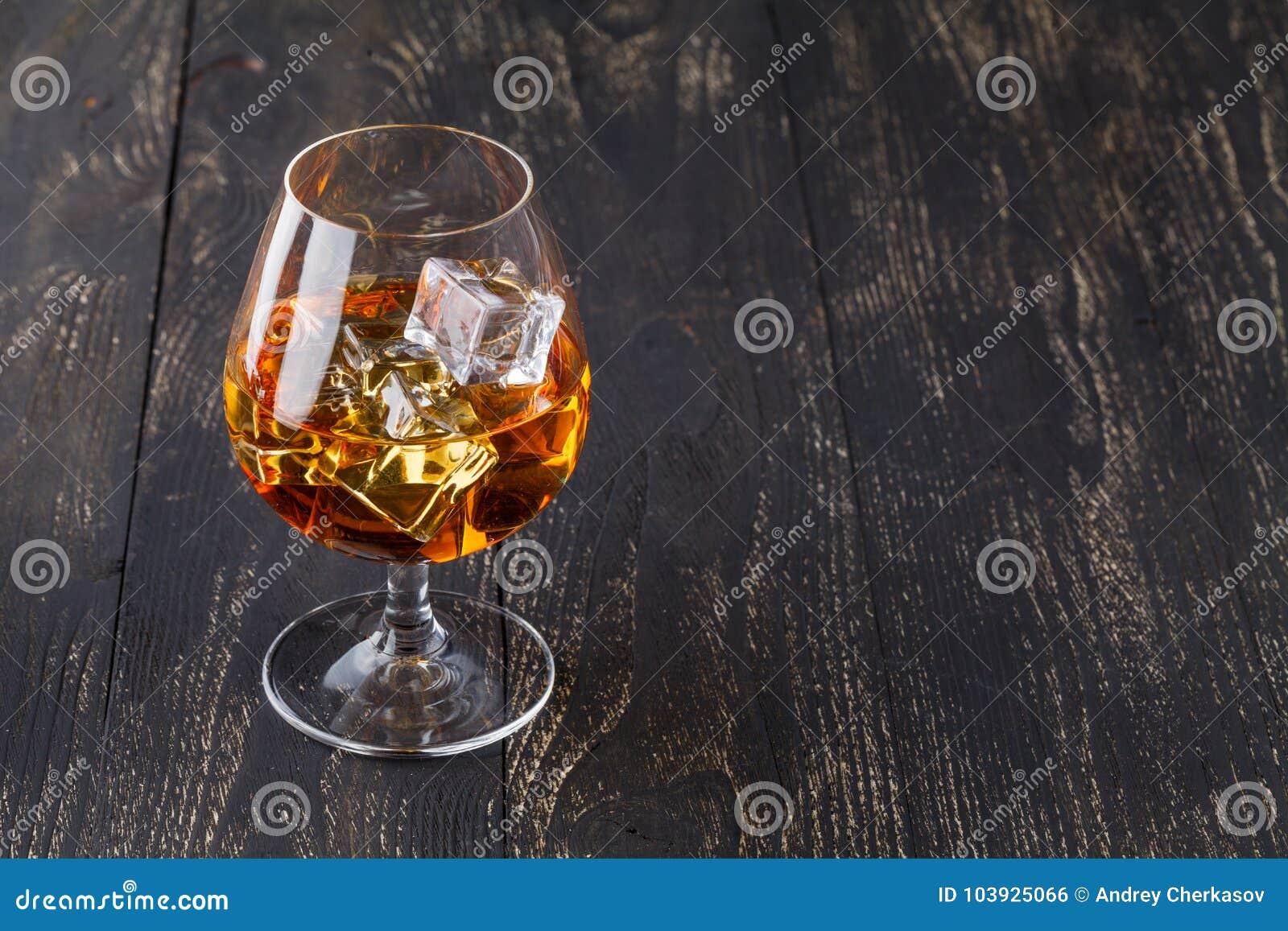 Glas whisky met ijsblokjes op houten planken worden gediend die Uitstekende countertop met hoogtepunt en een glas sterke drank
