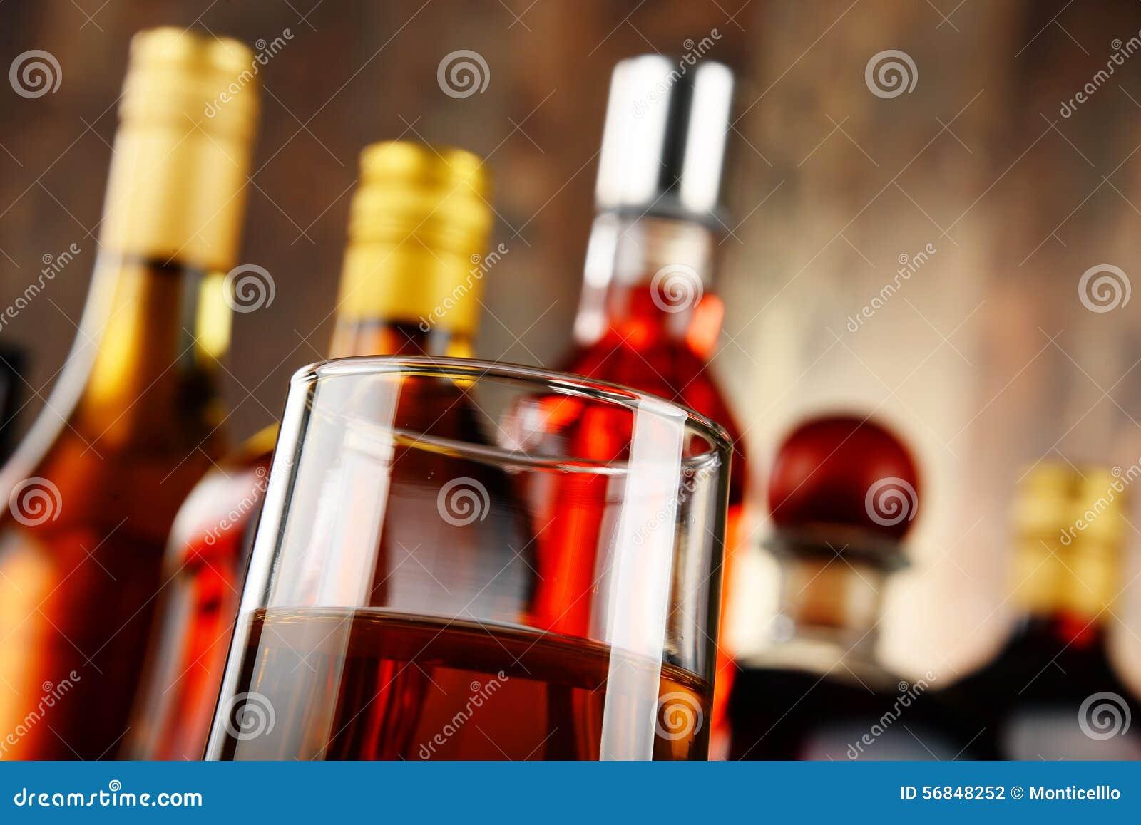 Glas Whisky und Flaschen sortierte alkoholische Getränke