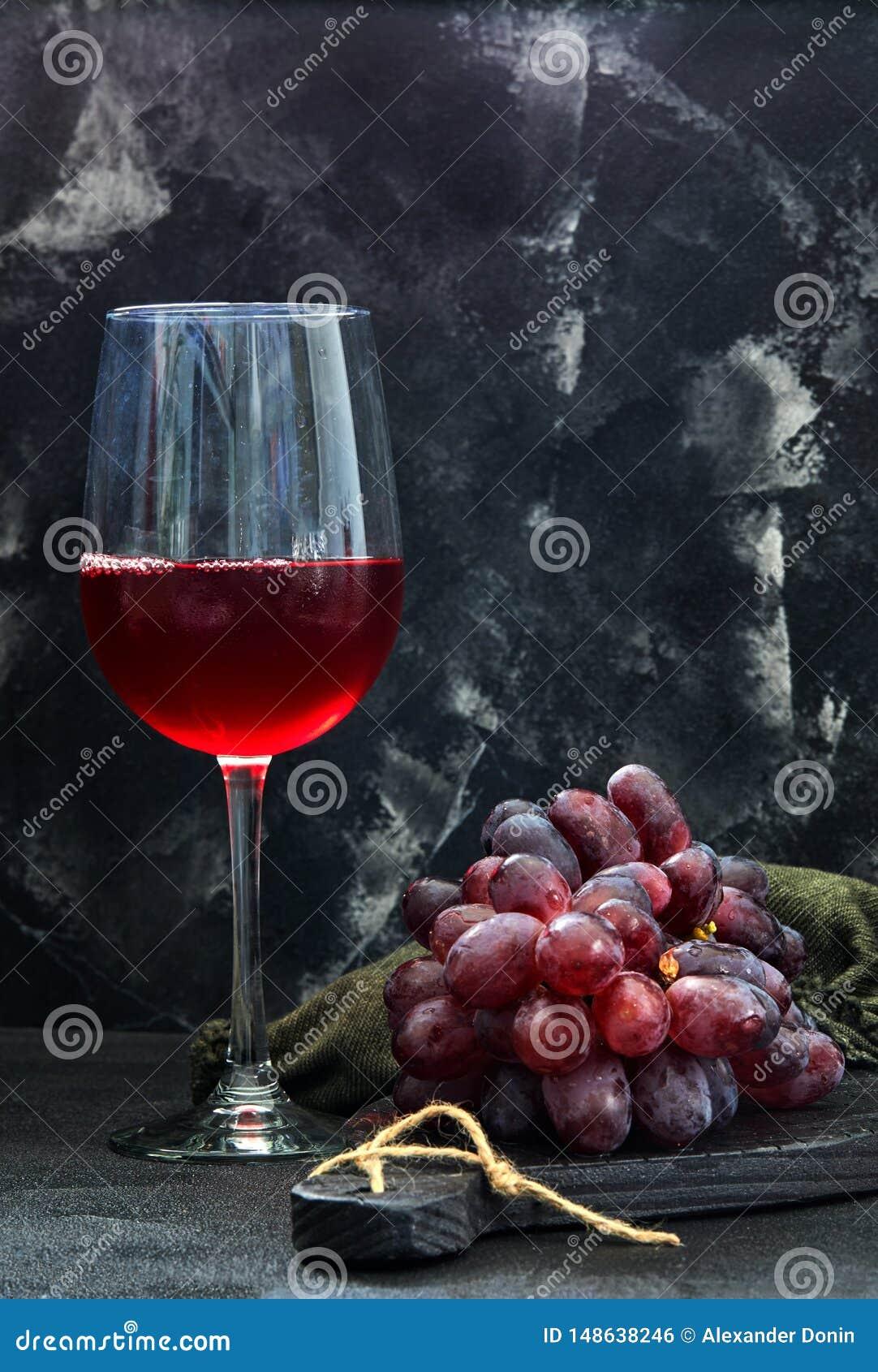 Glas wijn met druiven op een zwarte houten tribune