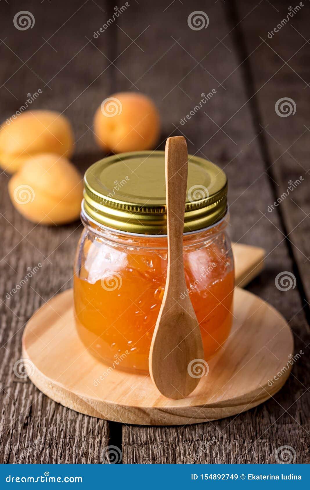 Glasgefäß selbst gemachte geschmackvolle Aprikosen-Marmelade und reife Aprikosen auf der hölzernen Hintergrund-Vertikale
