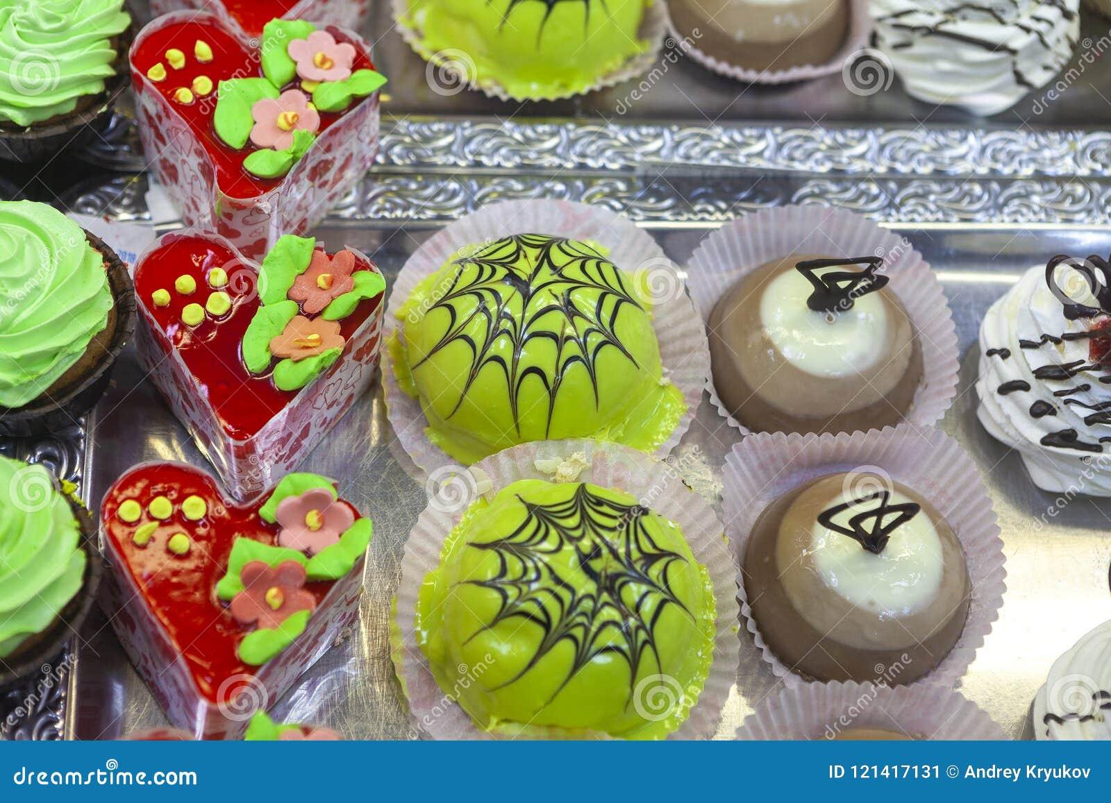 Glasig-glänzendes Grünes, Rot und Schokoladenkuchen mit Marmeladenblumen und Schokoladenbelag