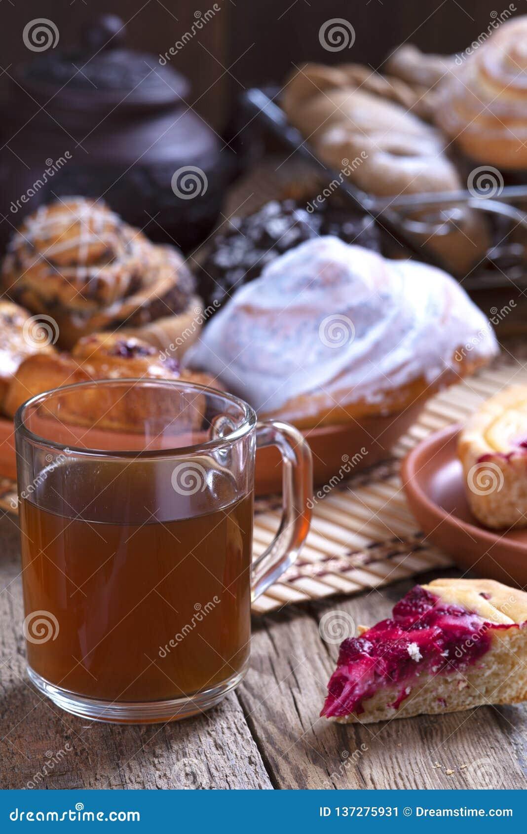 Glaskop thee en broodjes met papaver in een houten kop thee van het mandglas en broodjes met papaver