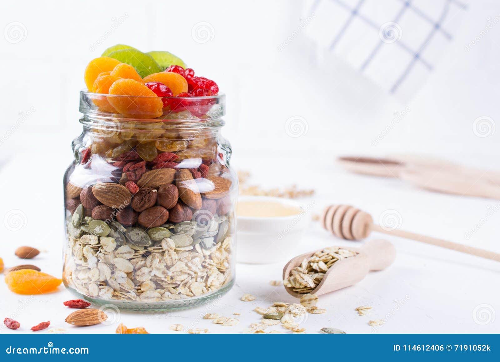 Glaskruik met ingrediënten voor het koken granola op witte achtergrond Havervlokken, honing, noten, gedroogd fruit en zaden