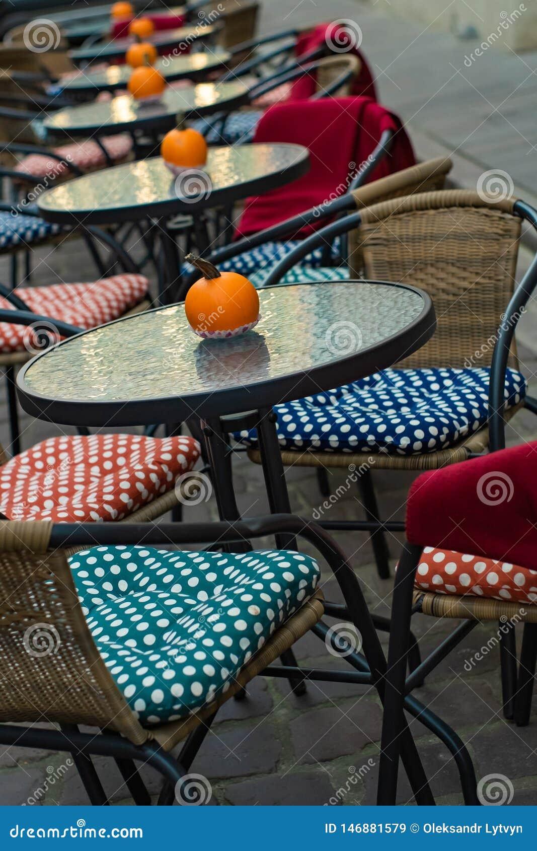 Glaslijsten van een openluchtkoffie met pompoenen en gekleurde kussens van stoelen