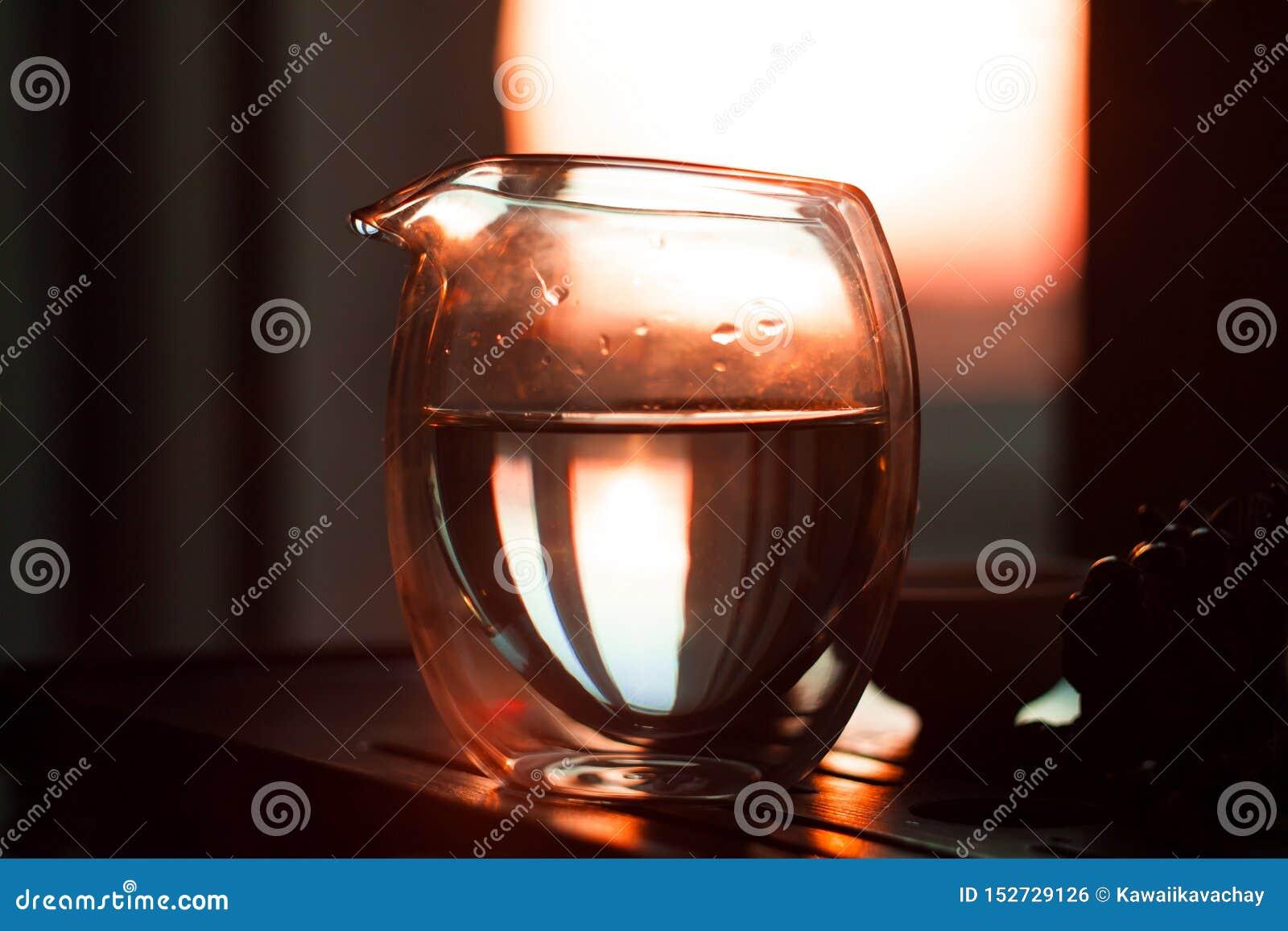 Glaspitcher heißer Tee auf Holztisch auf dem Hintergrund des schönen Sonnenuntergangs mit Sonnenstrahlen