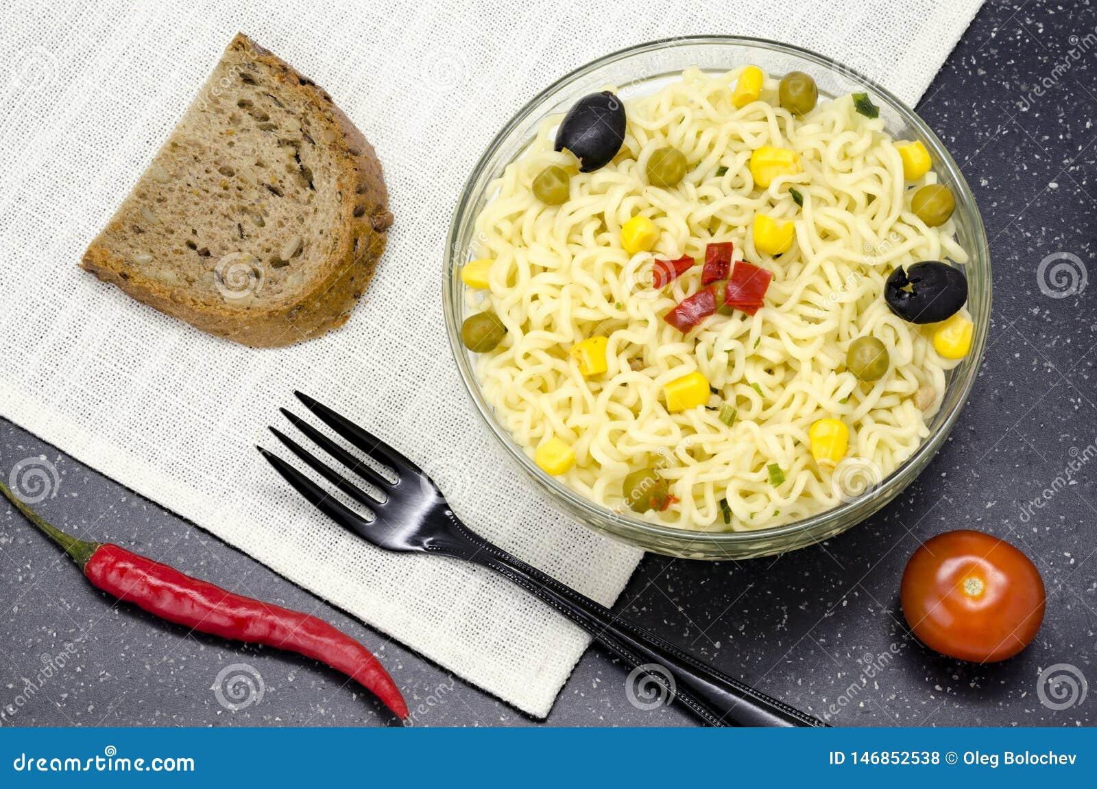 Glasplaat van noedels, vork, brood, Spaanse peper en tomaat